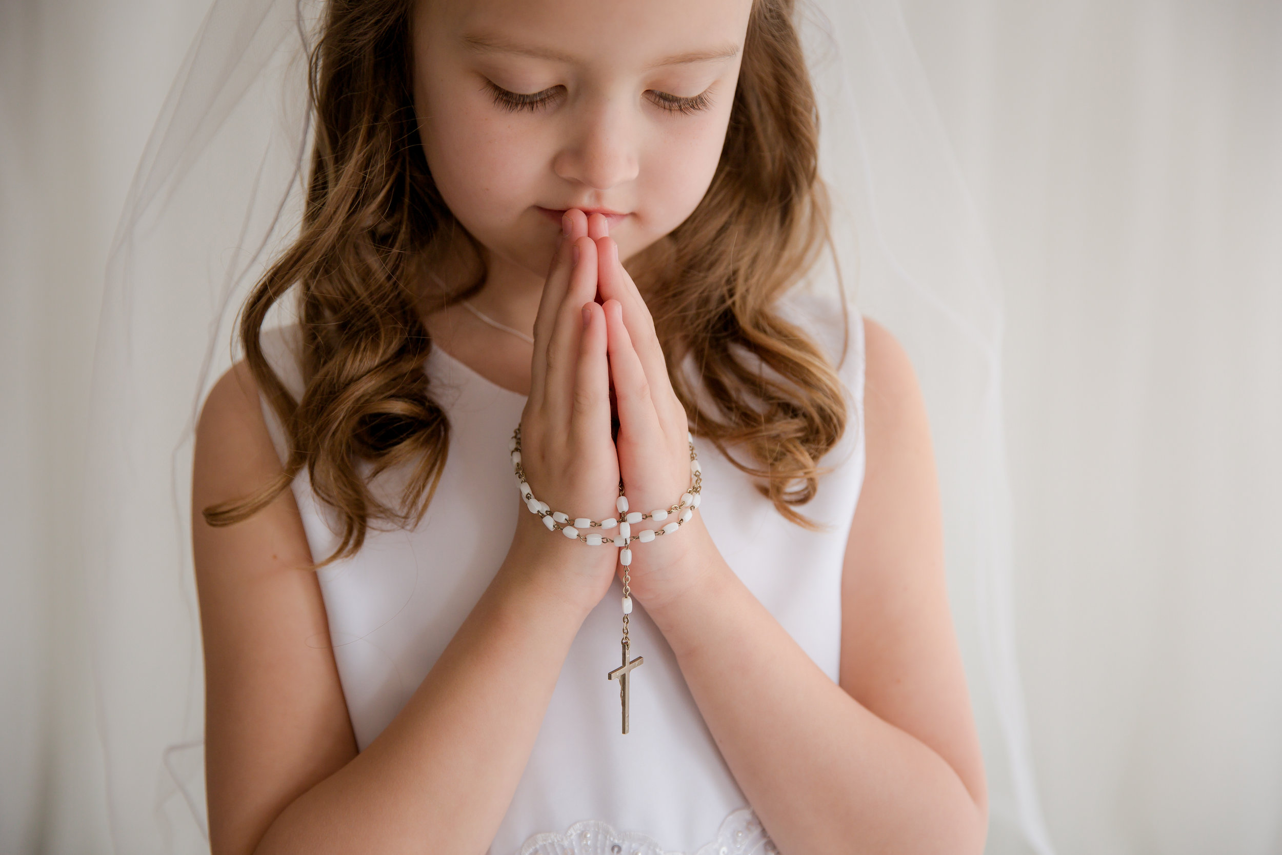 first holy communion girl wearing a white dress and a rosary praying