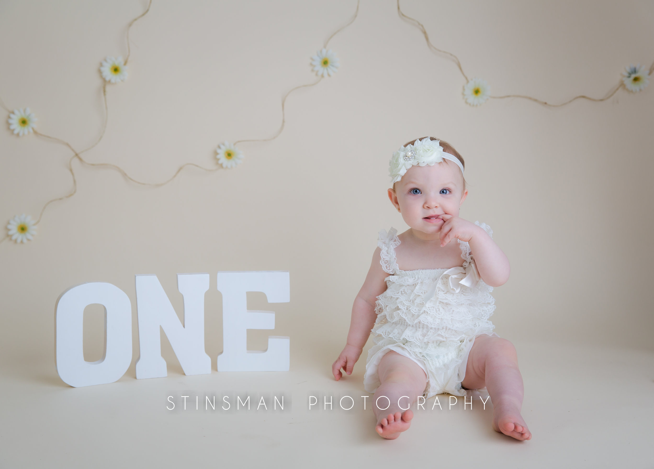 one year old birthday girl wearing white with a white headband and O N E letters