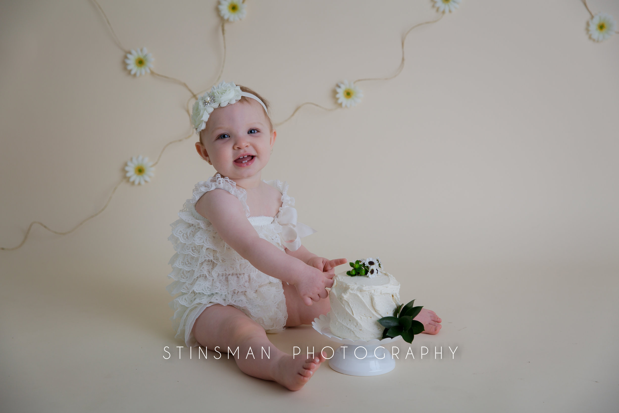 little girl poking her finger into her cake smash cake wearing white with a white headband