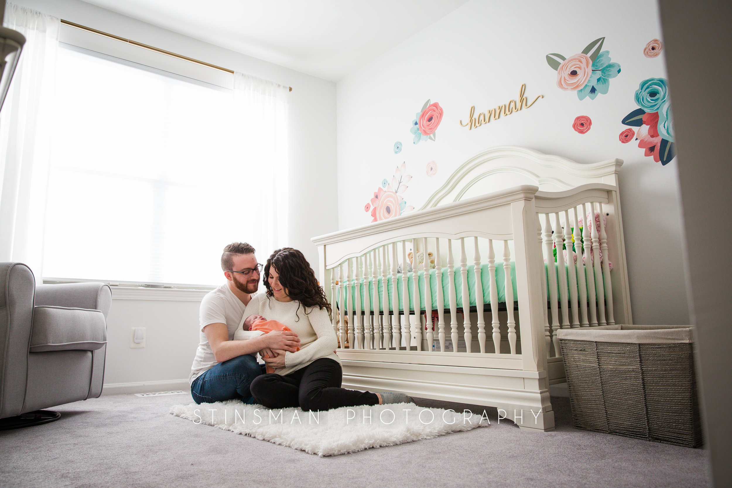 family wearing white shirts in robbinsville new jersey holding their new baby girl for their newborn session