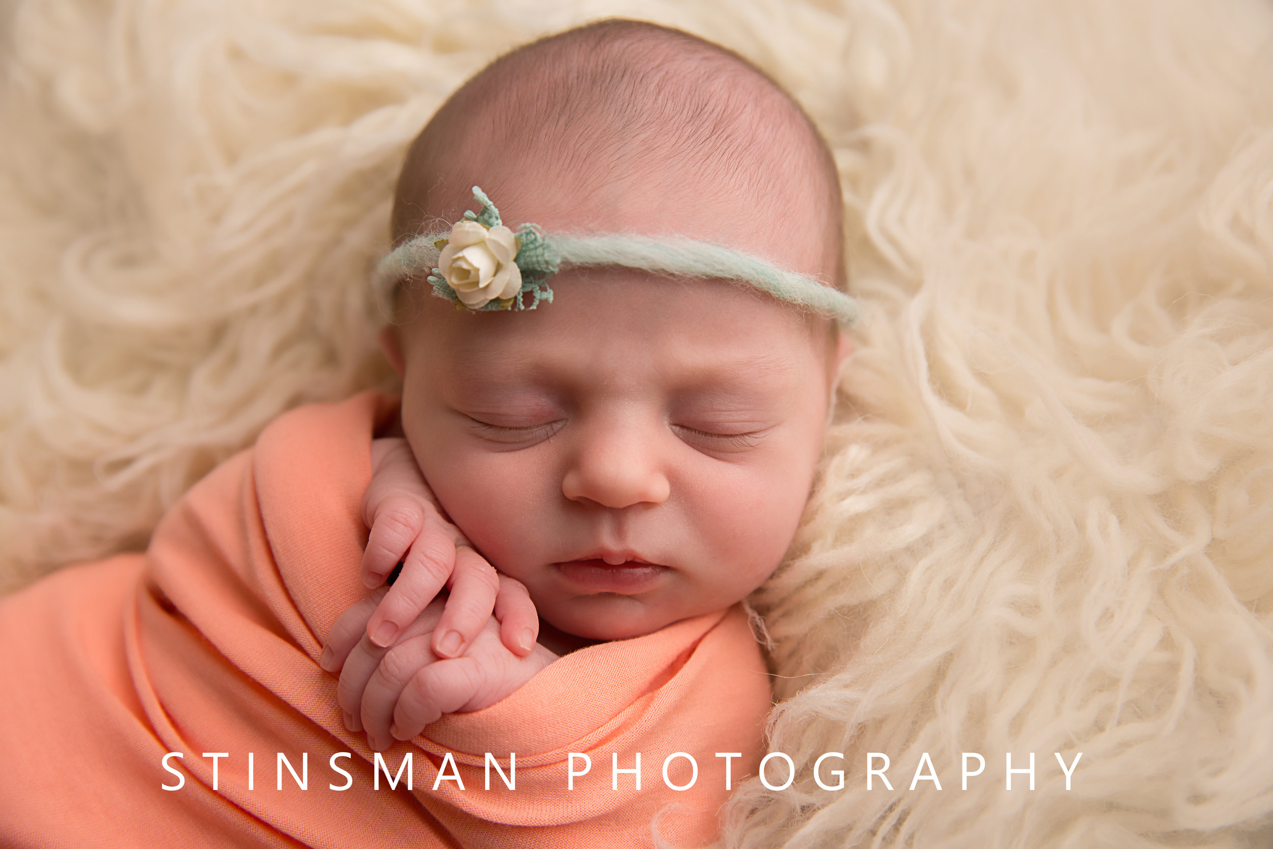 newborn baby girl wrapped in pink with a white and teal flower bow by stinsman photography in new jersey