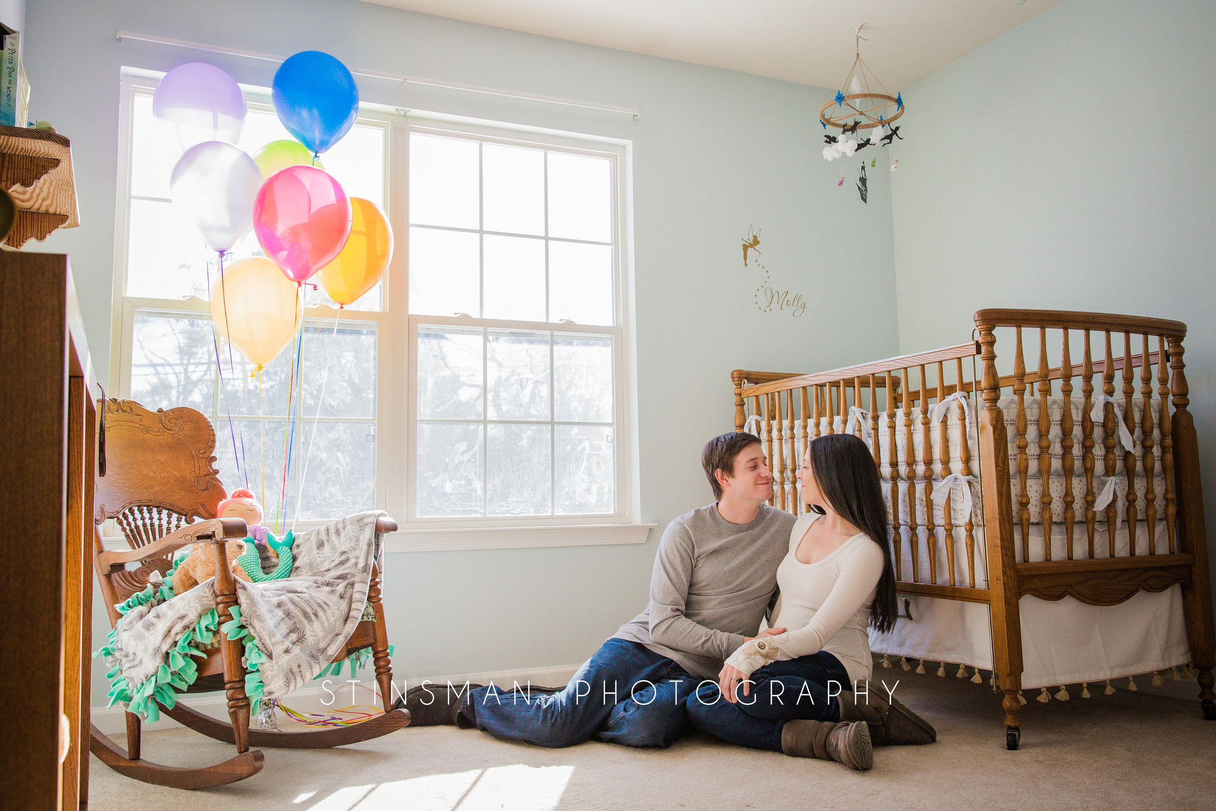 sitting the the baby's nursey for their maternity session in new jersey