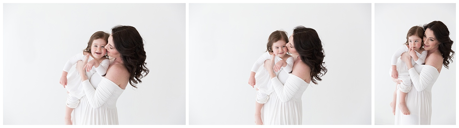 pregnant mom holding her 2 year old daughter wearing a white gown in burlington nj for pregnancy photos