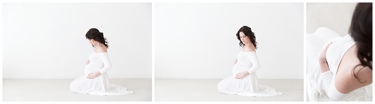 pregnant mom kneeling on the floor looking at her pregnant belly for pregnancy photos