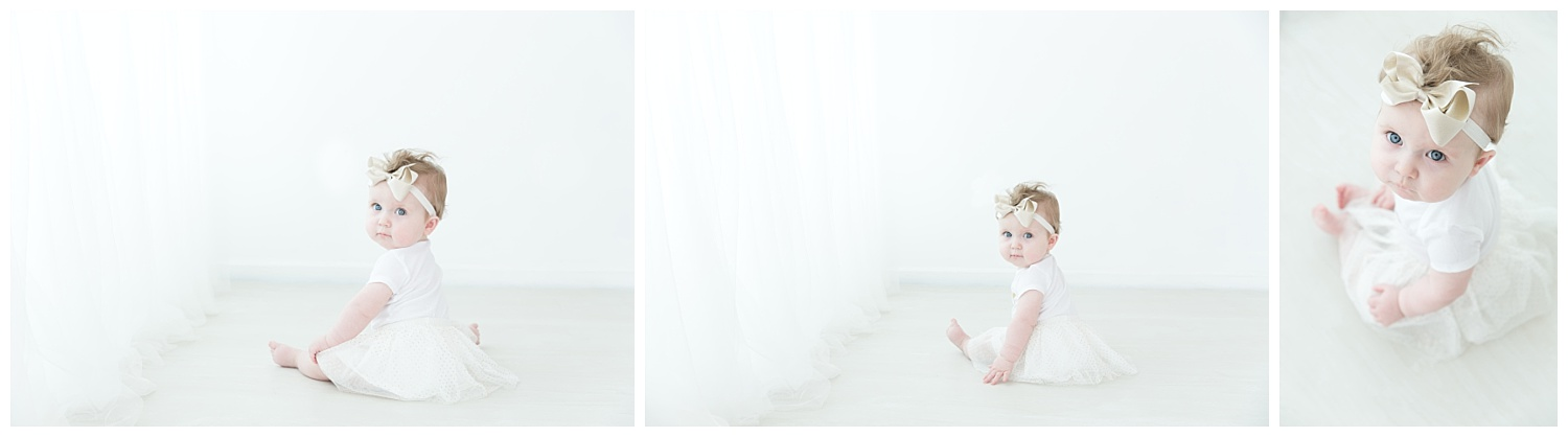 little girl one year old wearing white and a gold bow for her birthday photos in burlington nj