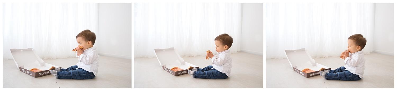 little boy eating pizza in front of the window in burlington new jersey studio