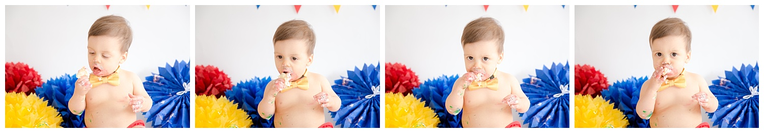 little boy smashing his cake for his first birthday photos