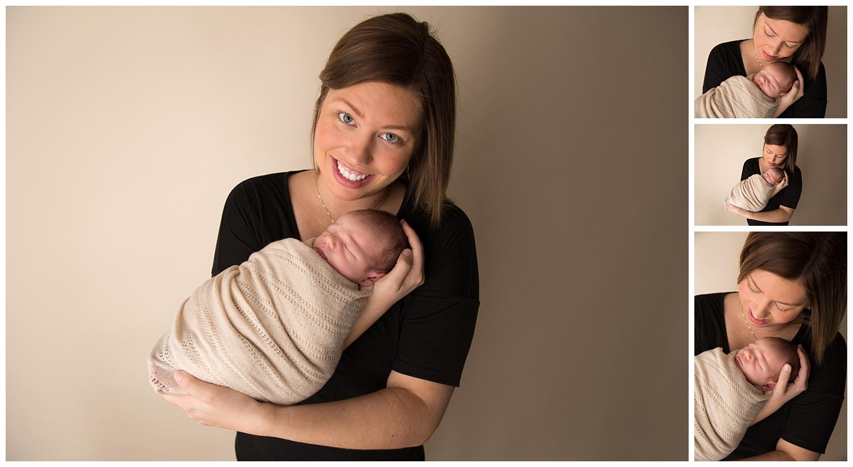 mom holding newborn baby boy in a black shirt and cream wrap in newborn photo studio in burlington new jersey