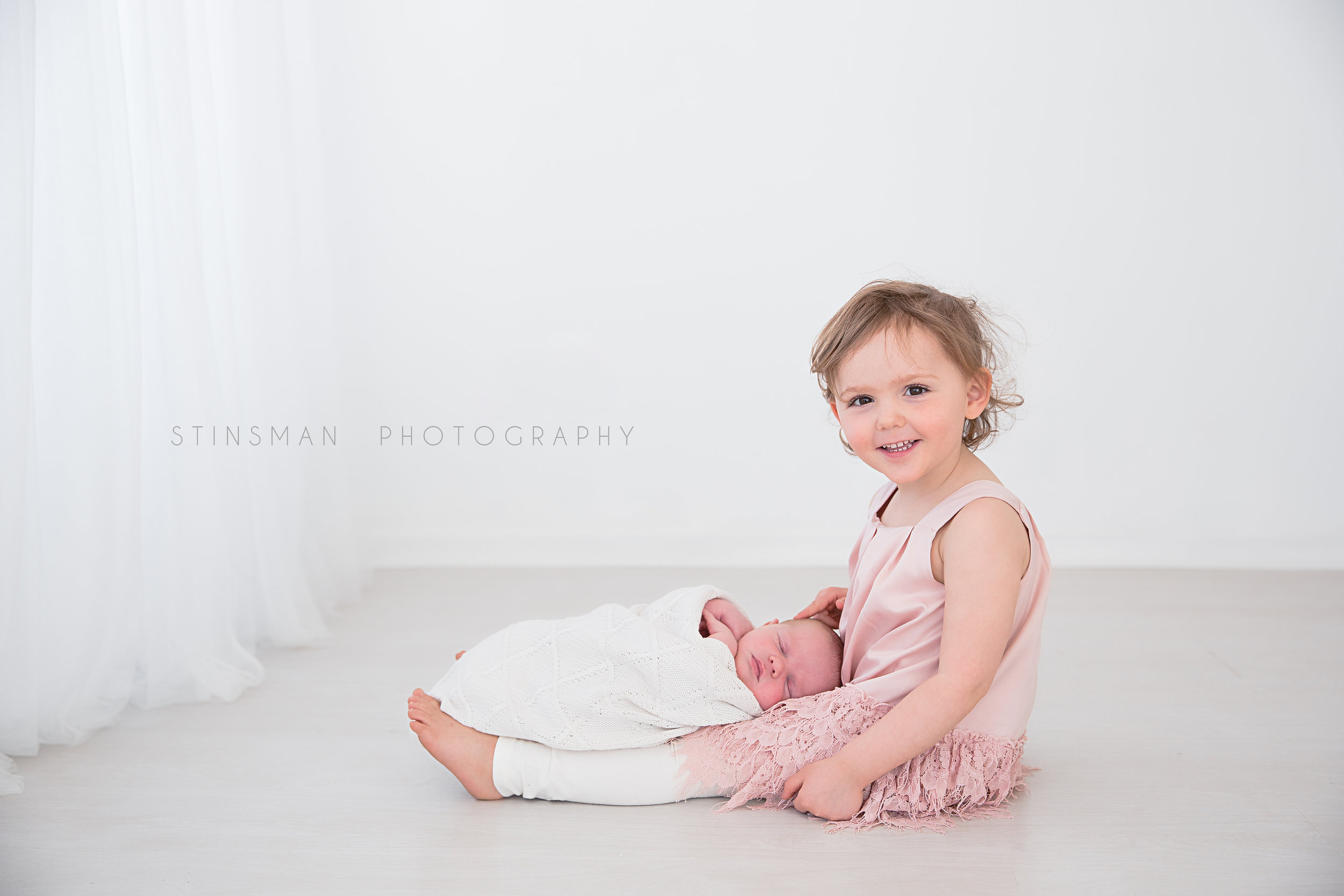 big sister and newborn photos in white studio in burlington new jersey