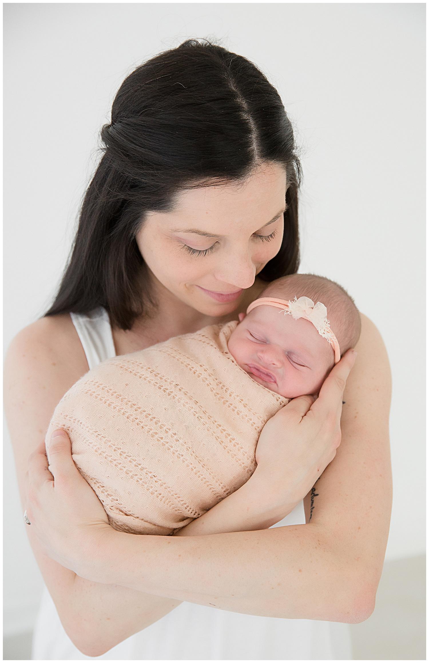 mom kissing her newborn baby girl in burlington new jersey newborn photo shoot