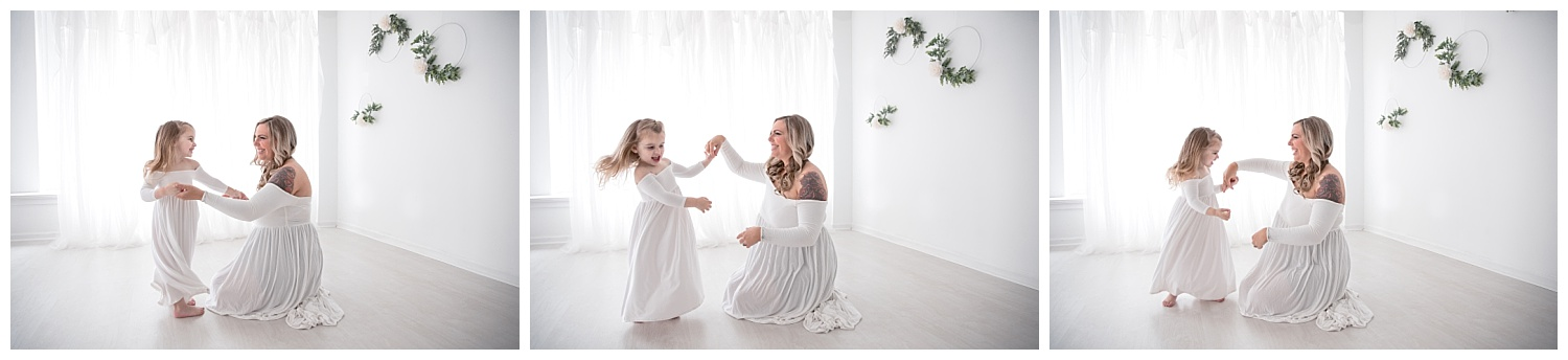 mom and daughter dancing together in white dresses for burlington nj photo shoot