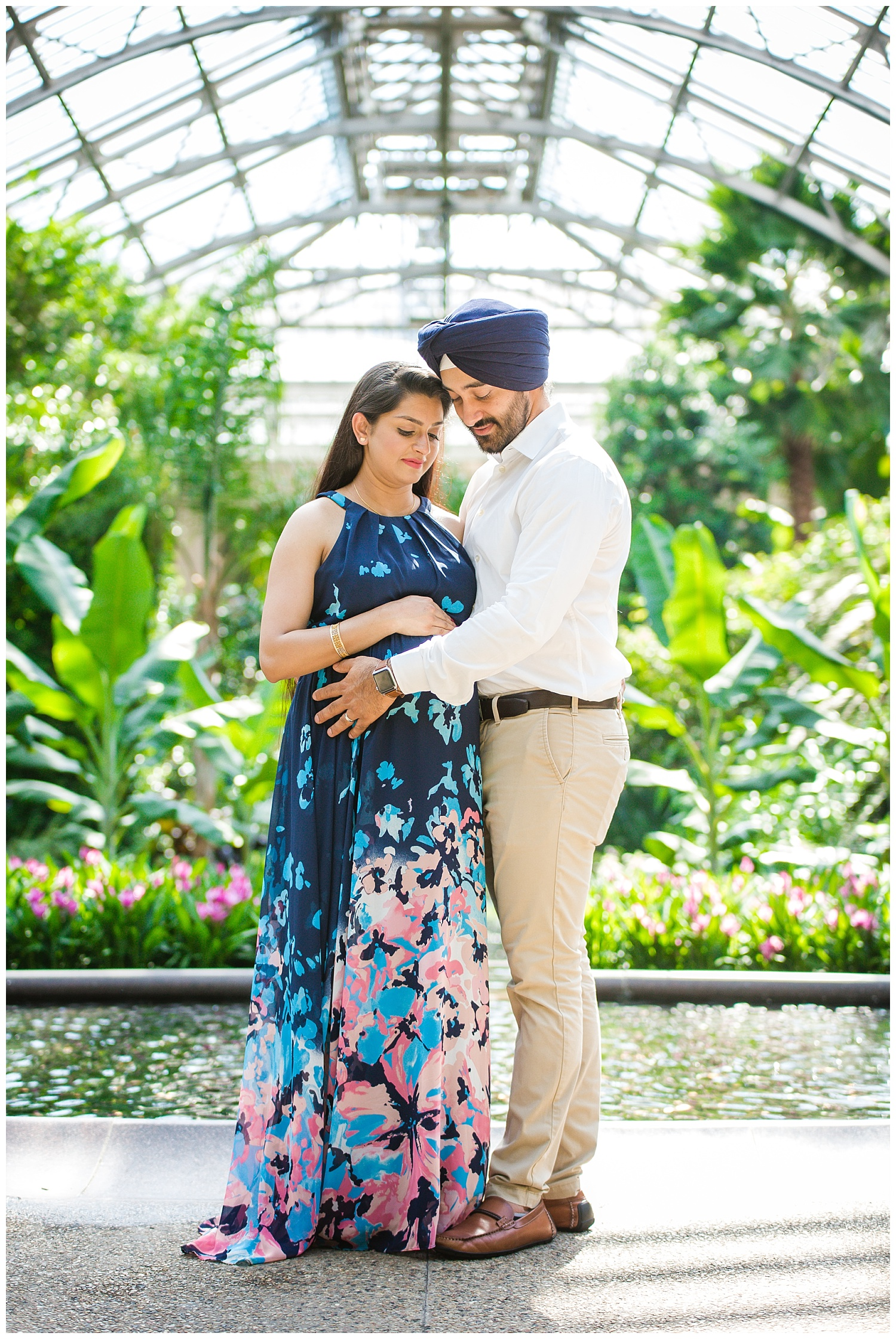 husband and wife looking at her pregnant belly at longwood gardens pa