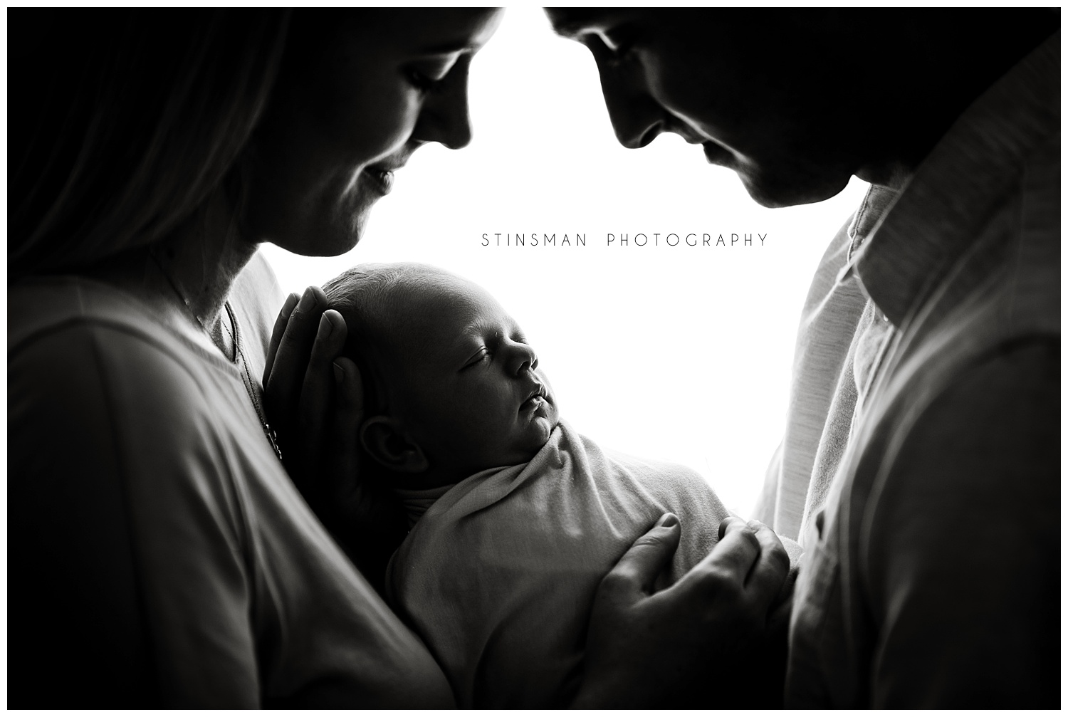 beautiful black and white photo of mom and dad holding newborn baby boy in moorestown nj studio