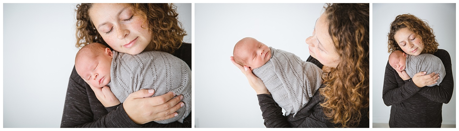 mom holding her newborn baby boy named chris in a grey wrap in burlington new jersey and moorestown baby studio