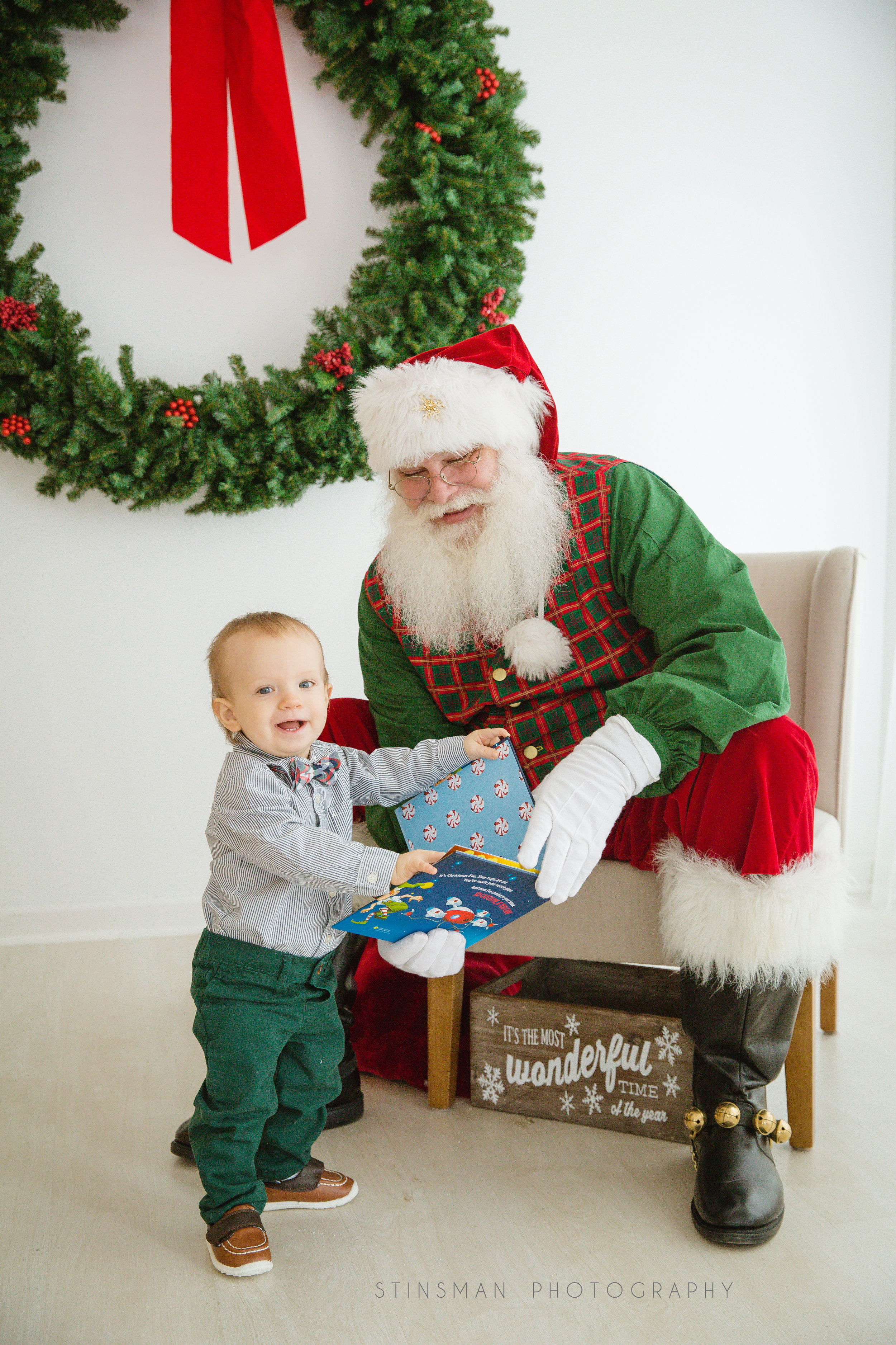 baby boy smiling while reading a book with santa in burlington new jersey photo studio