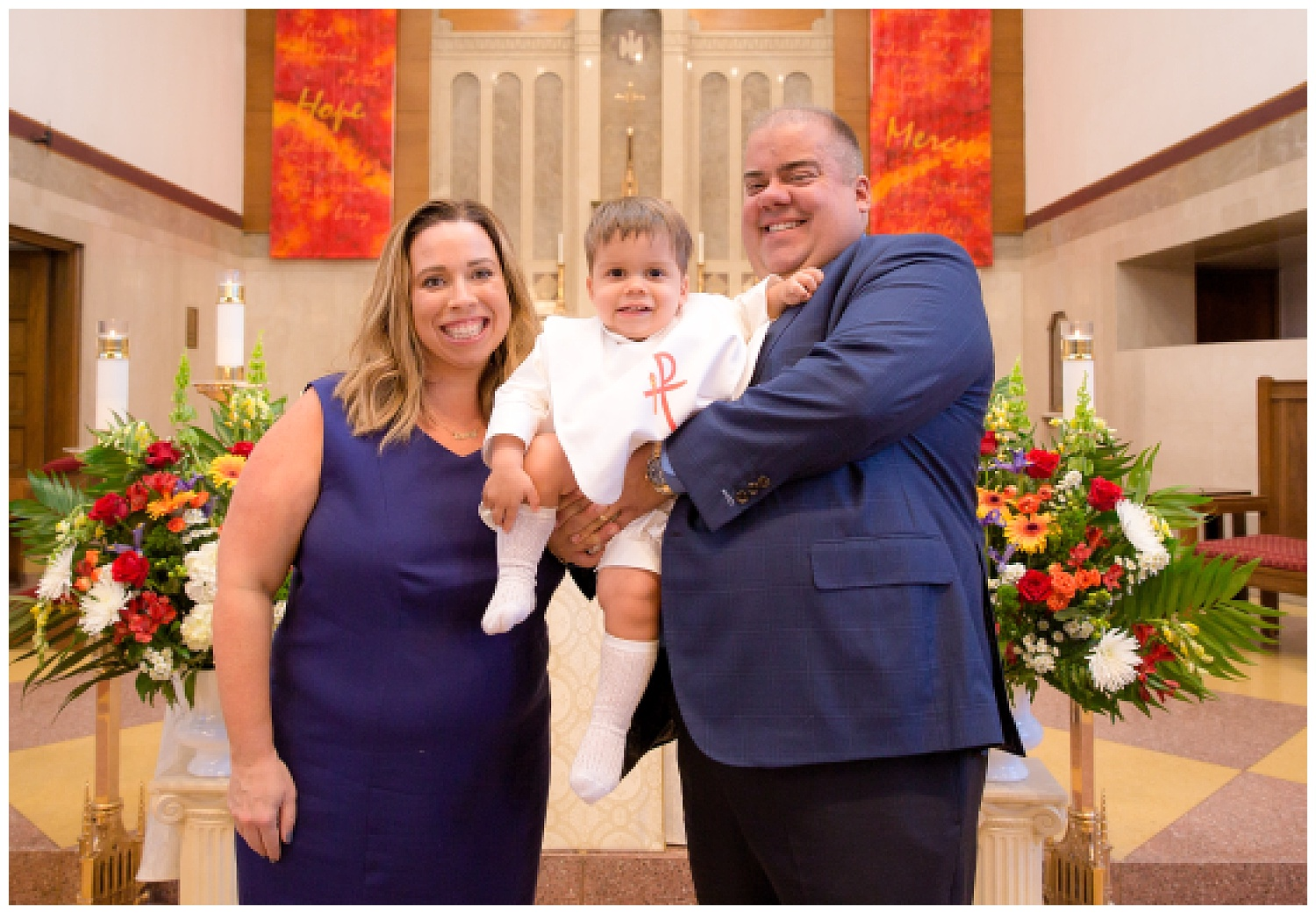 mom and dad holding his son after baptism in haddonfield new jersey church
