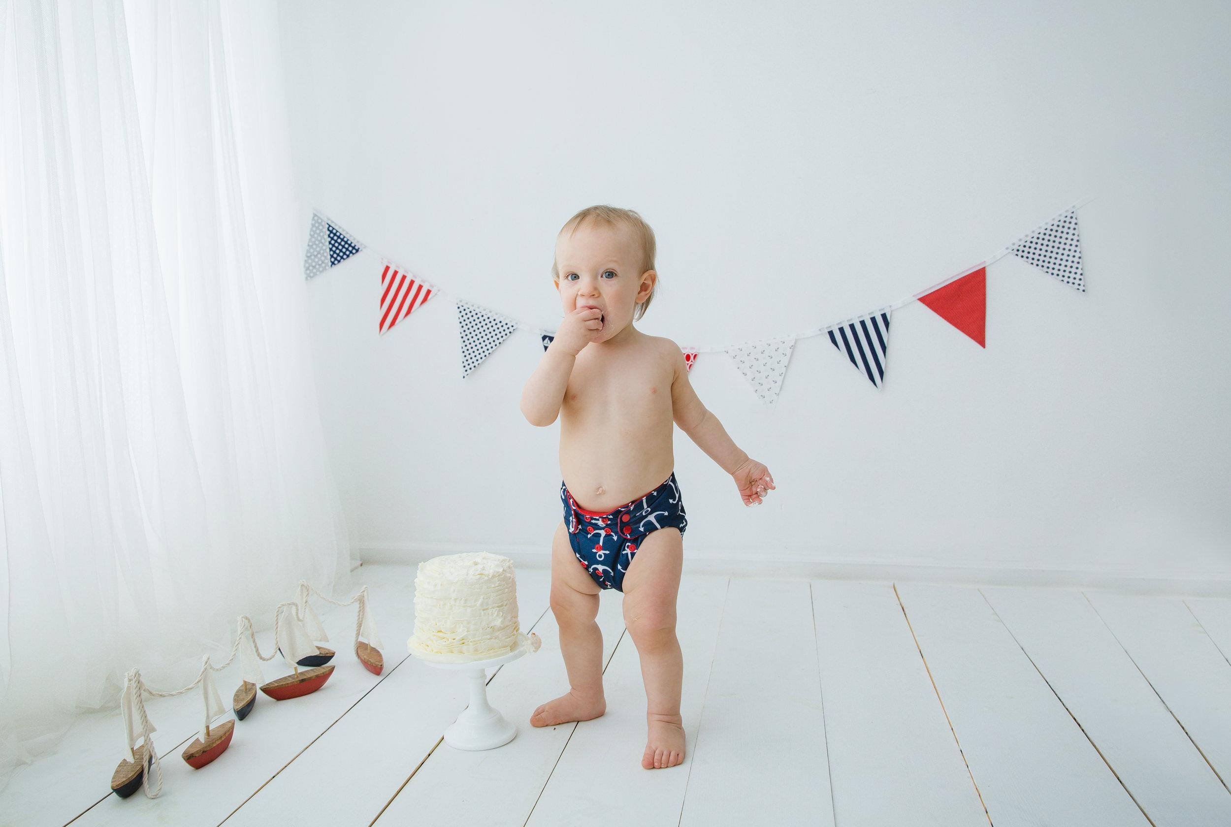 little boy with a nautical cake smash theme eating his cake in burlington nj photo studio