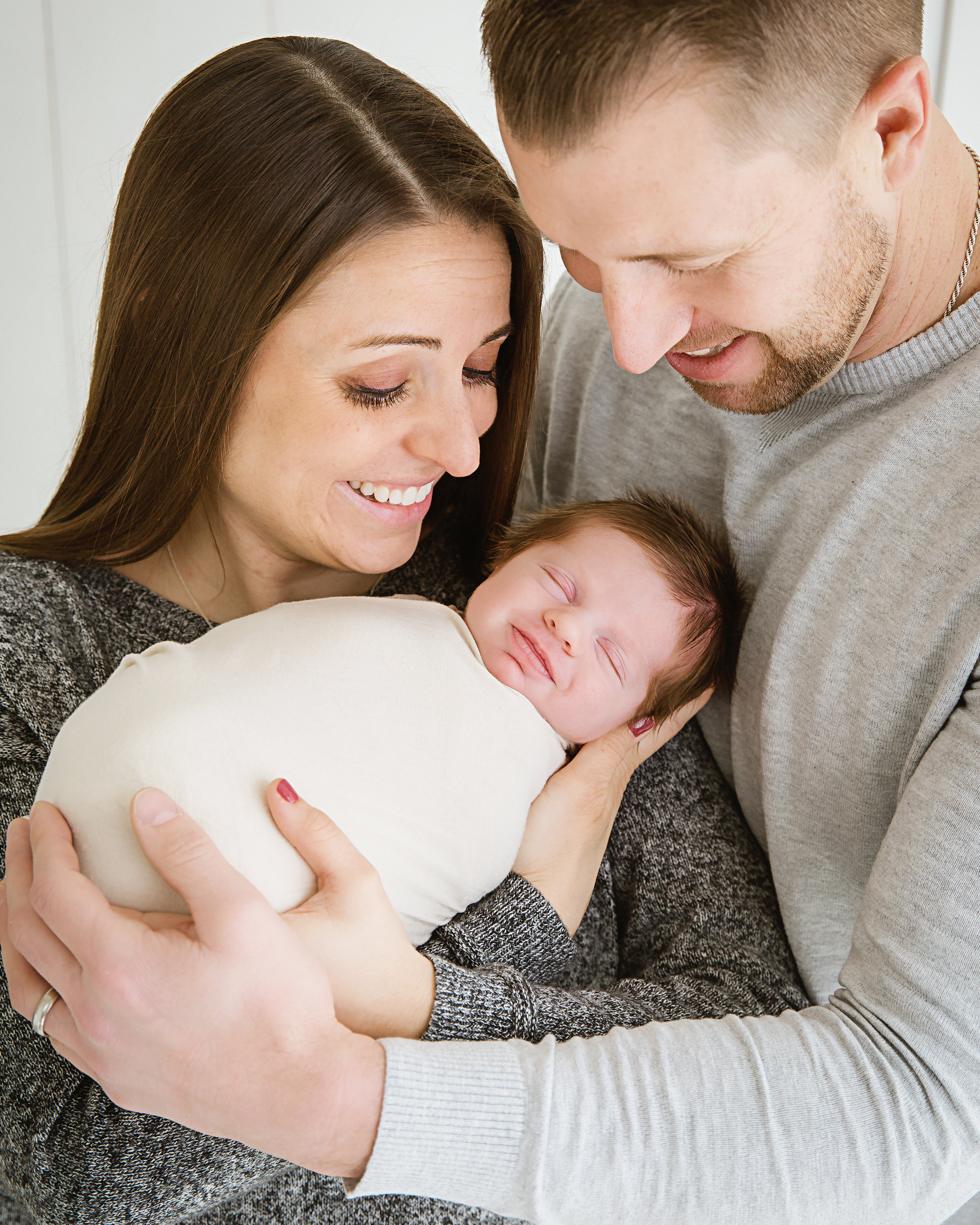 Mom and dad holding their beautiful smiling baby boy in Burlington nj photo studio