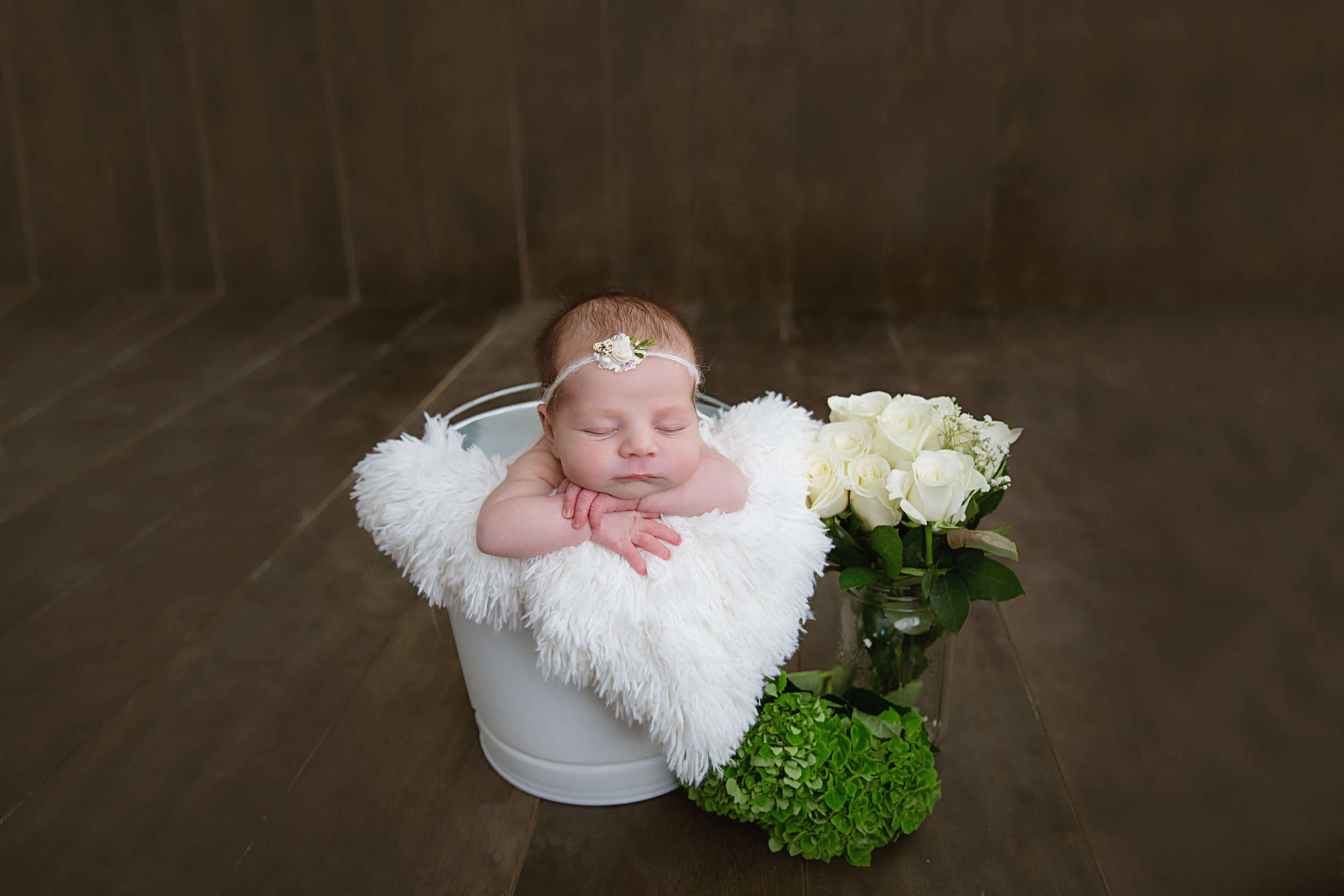 baby girl in a bucket and white roses