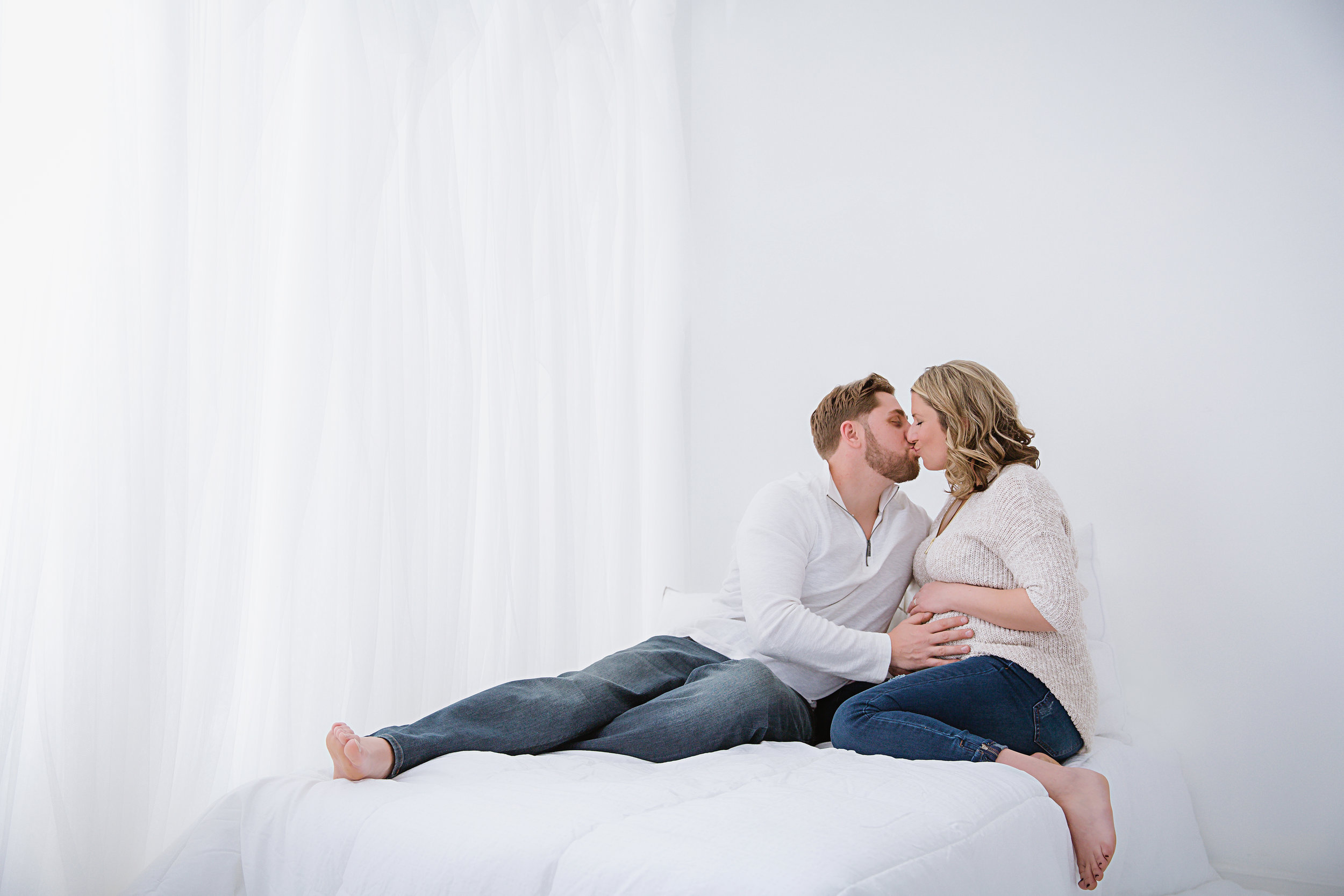 in-studio-maternity-photo-shoot-wearing-white-sweaters-in-bed