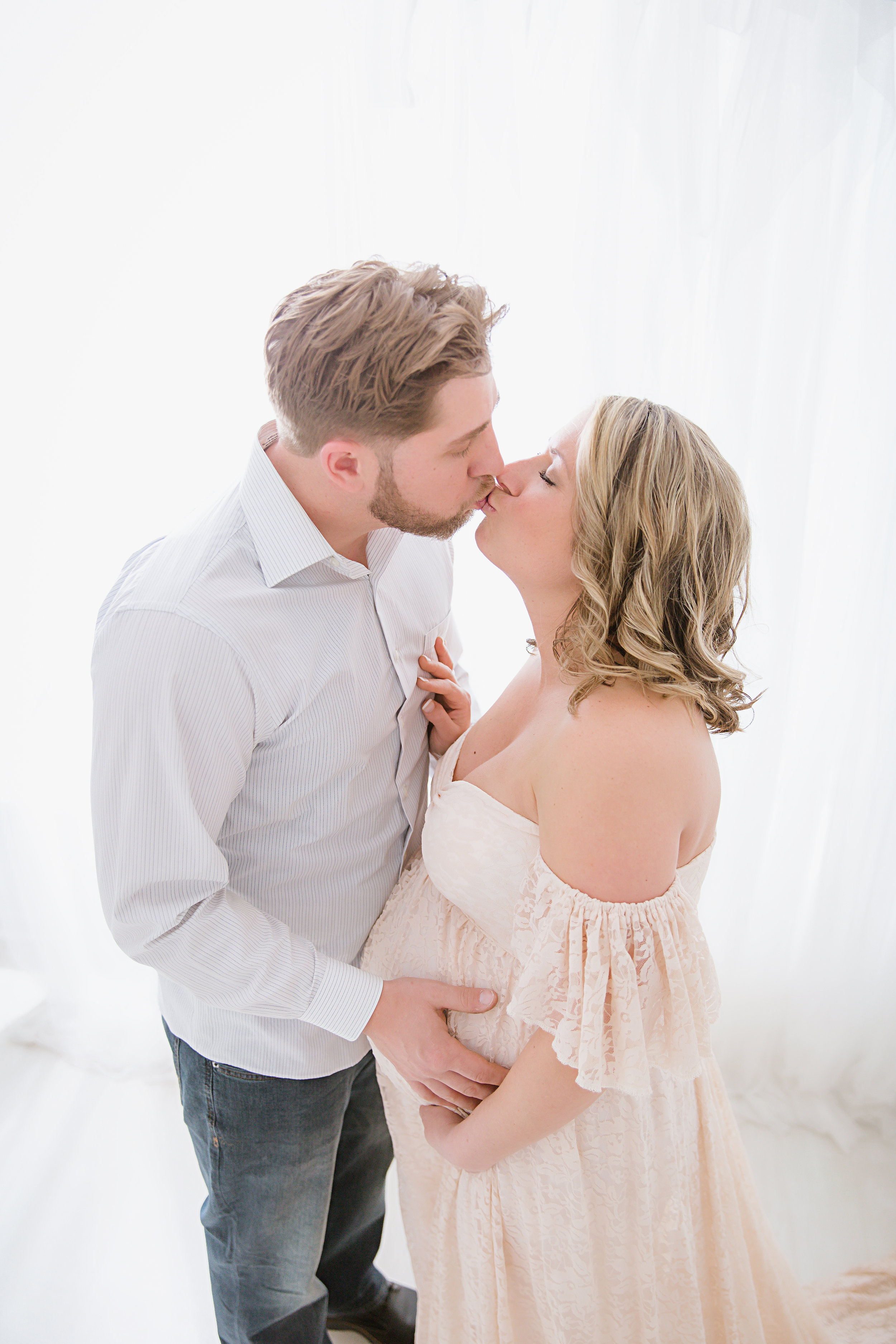 in-studio-maternity-session-with-mom-and-dad-kissing-eachother-while-holding-belly