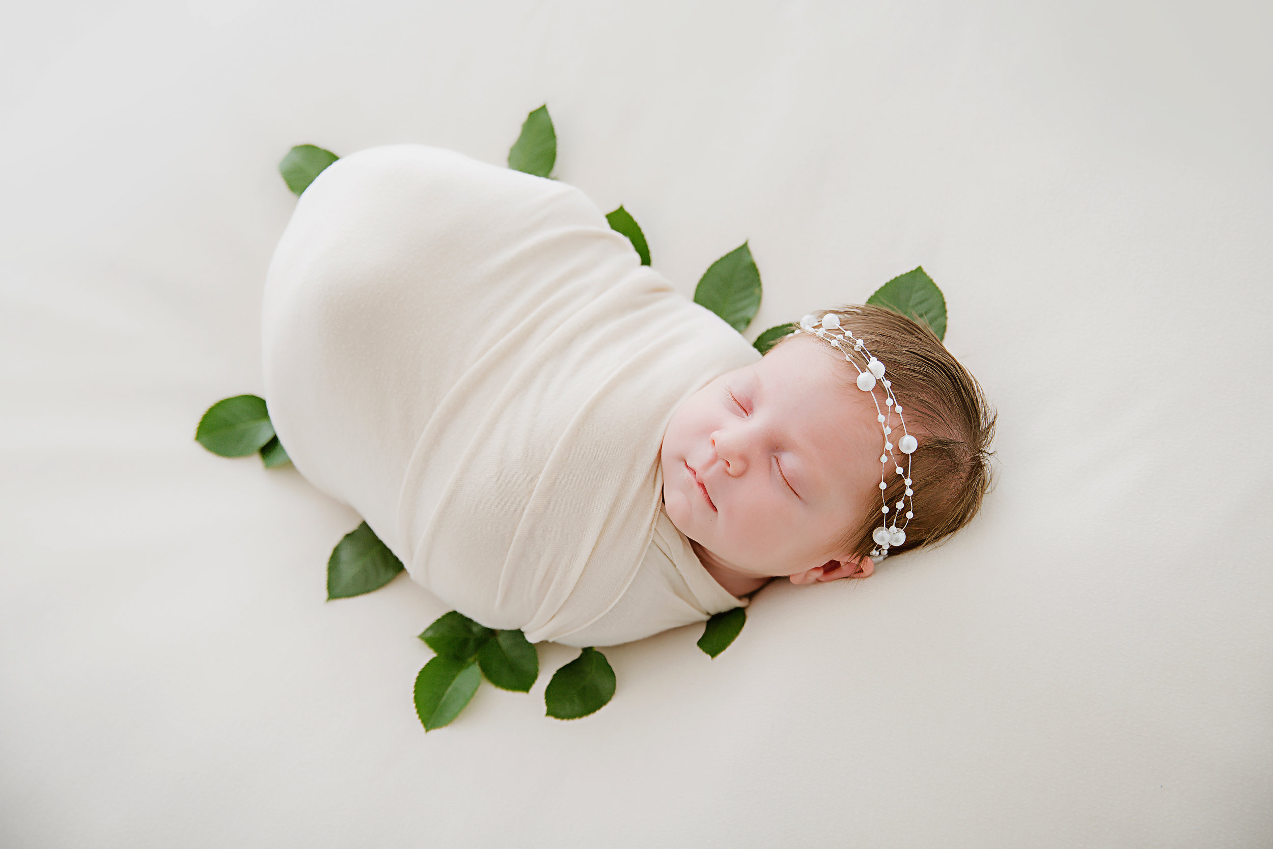 newborn-baby-girl-wrapped-in-white-over-head-photography-shot-lying-on-greenery-new-jersey