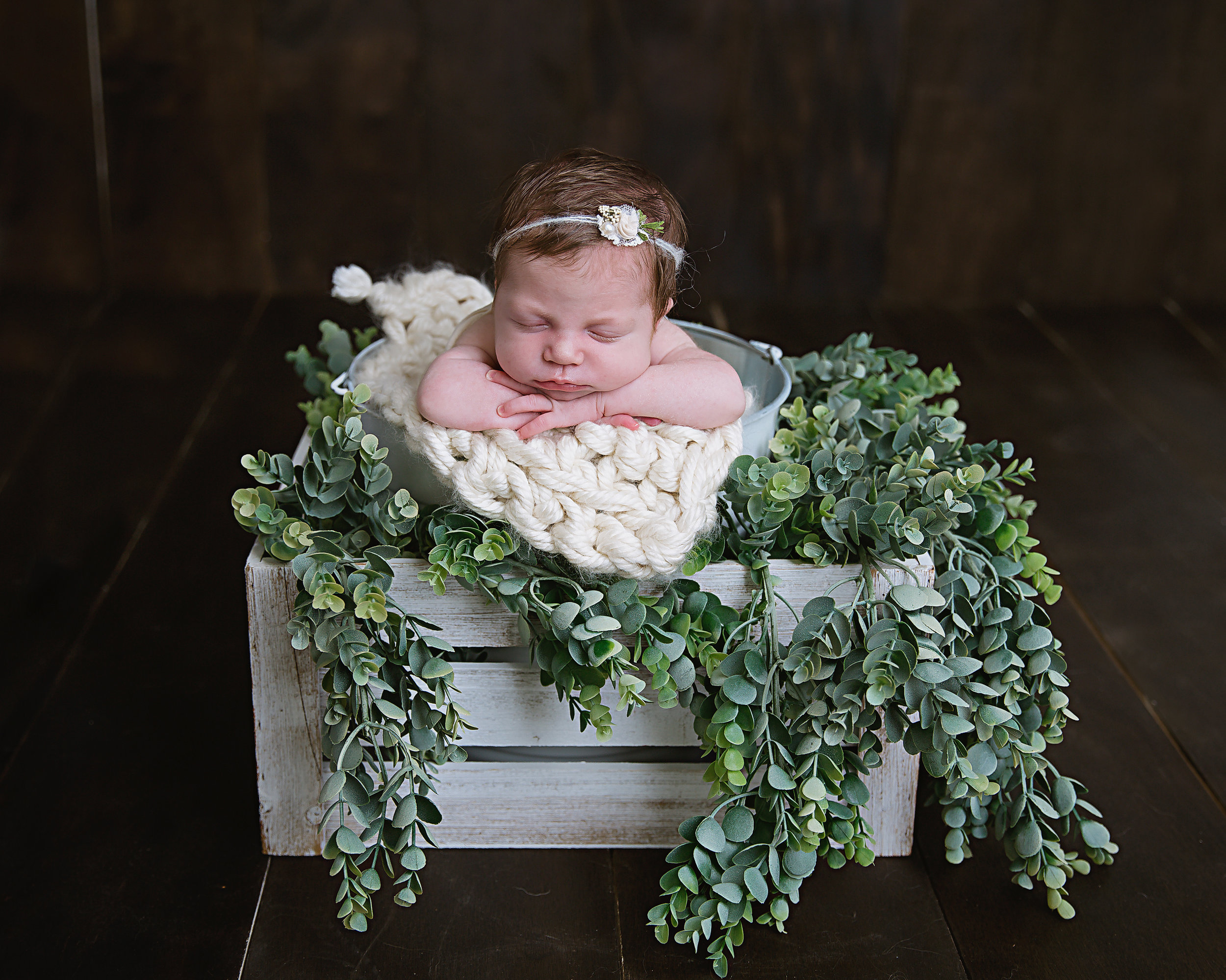 newborn-baby-girl-photography-shoot-lying-on-blanket-and-box-of-natural-greenery-black-background-new-jersey
