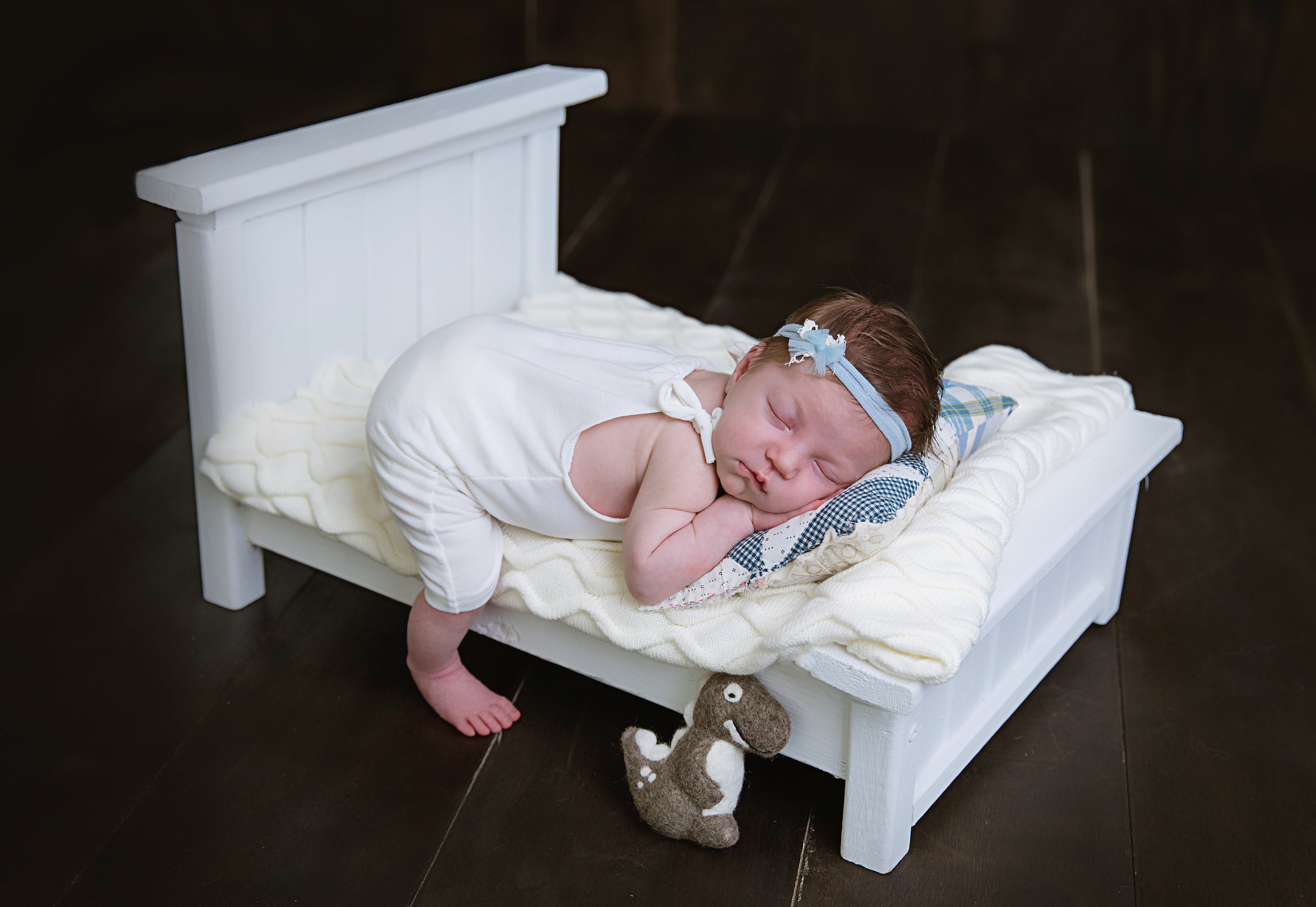 newborn-baby-girl-lying-on-soft-dream-bed-black-background-photography-blue-headband-shoot-burlington-new-jersey