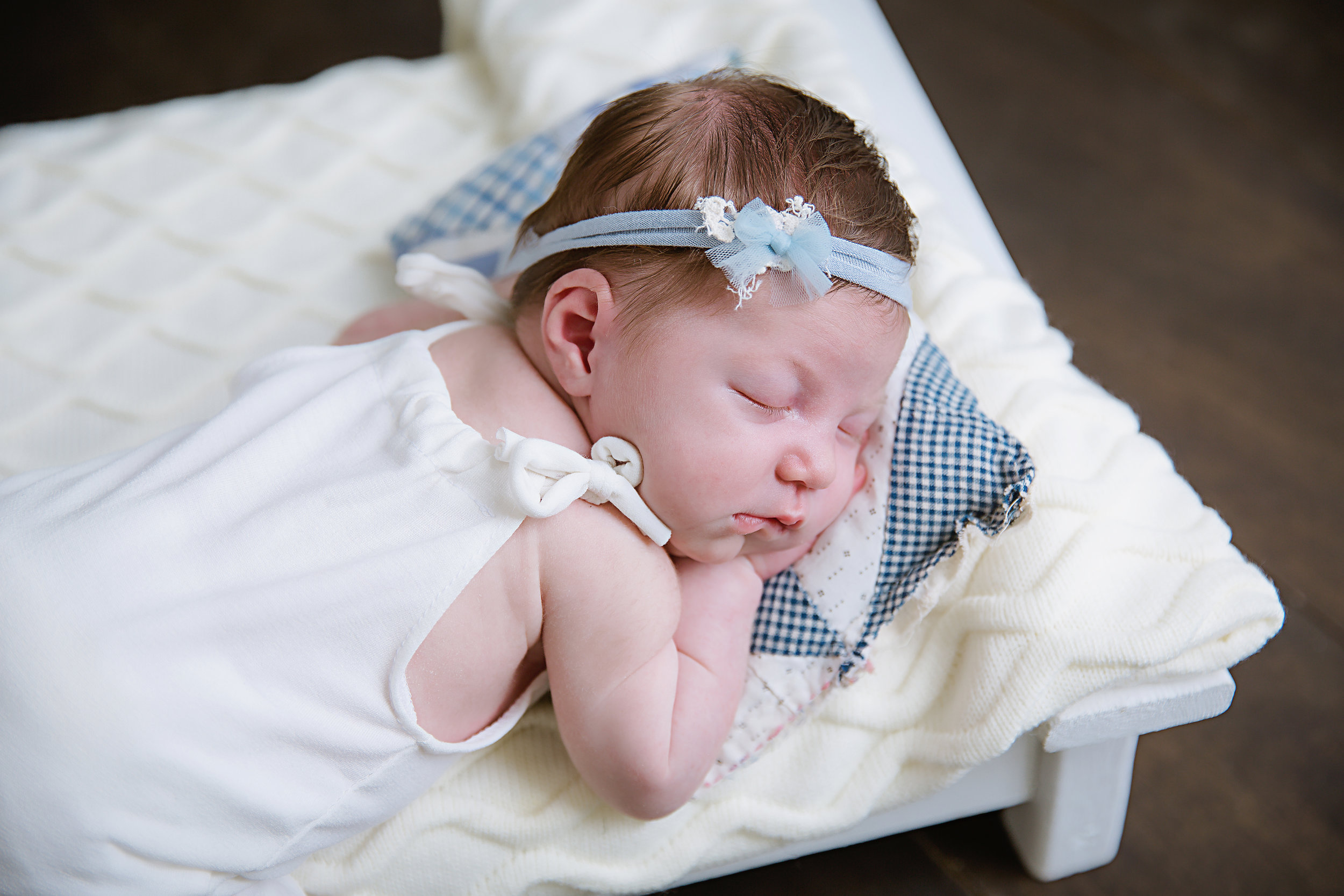 newborn-baby-girl-dressed-in-white-lying-on-bed-sleeping-peacefully-photography-shoot-new-jersey