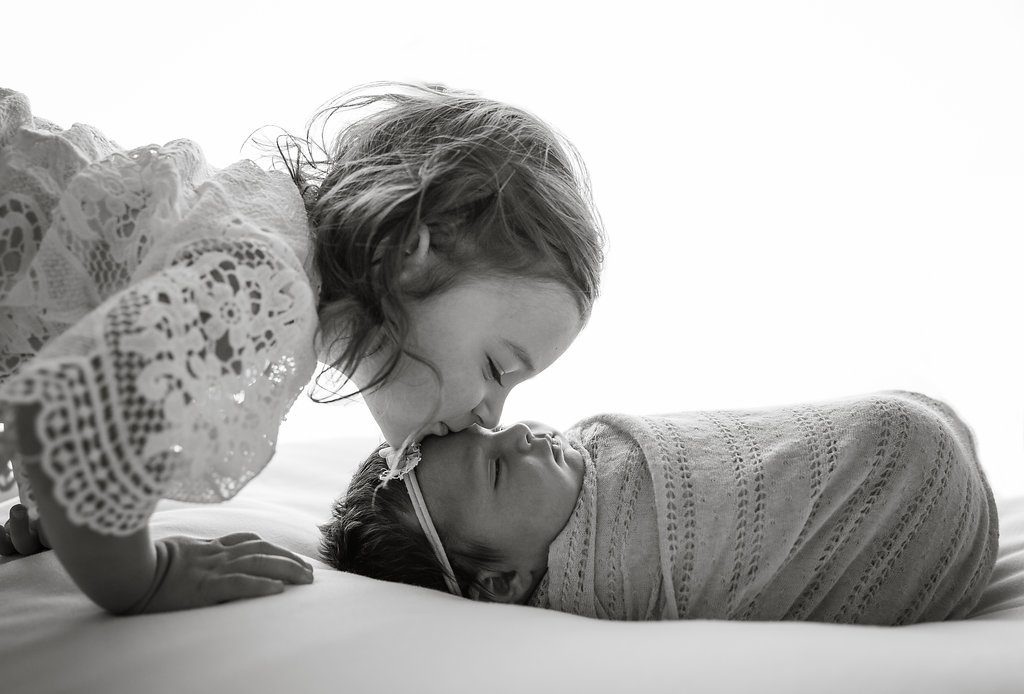 An older sister is tenderly kissing her younger sister's forehead. Photo taken in black and white. The newborn baby girl is sleeping peacefully while wrapped up in a blanked. She's also wearing a headband. Taken by a family photographer in New Jersey.