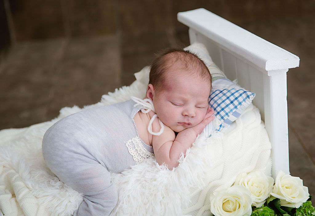 Sleeping peacefully on a tiny white bed, this newborn girl is surrounded by flowers. She's located in a wooden decorated studio in New Jersey.
