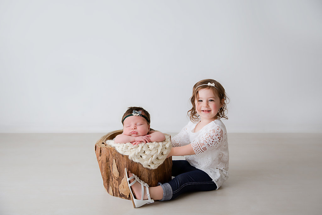 A big sister sitting next to her little newborn baby sister. The newborn is sitting in a wooden chair. She's lying on top of a knitted blanked. Taken by a newborn new jersey photographer.