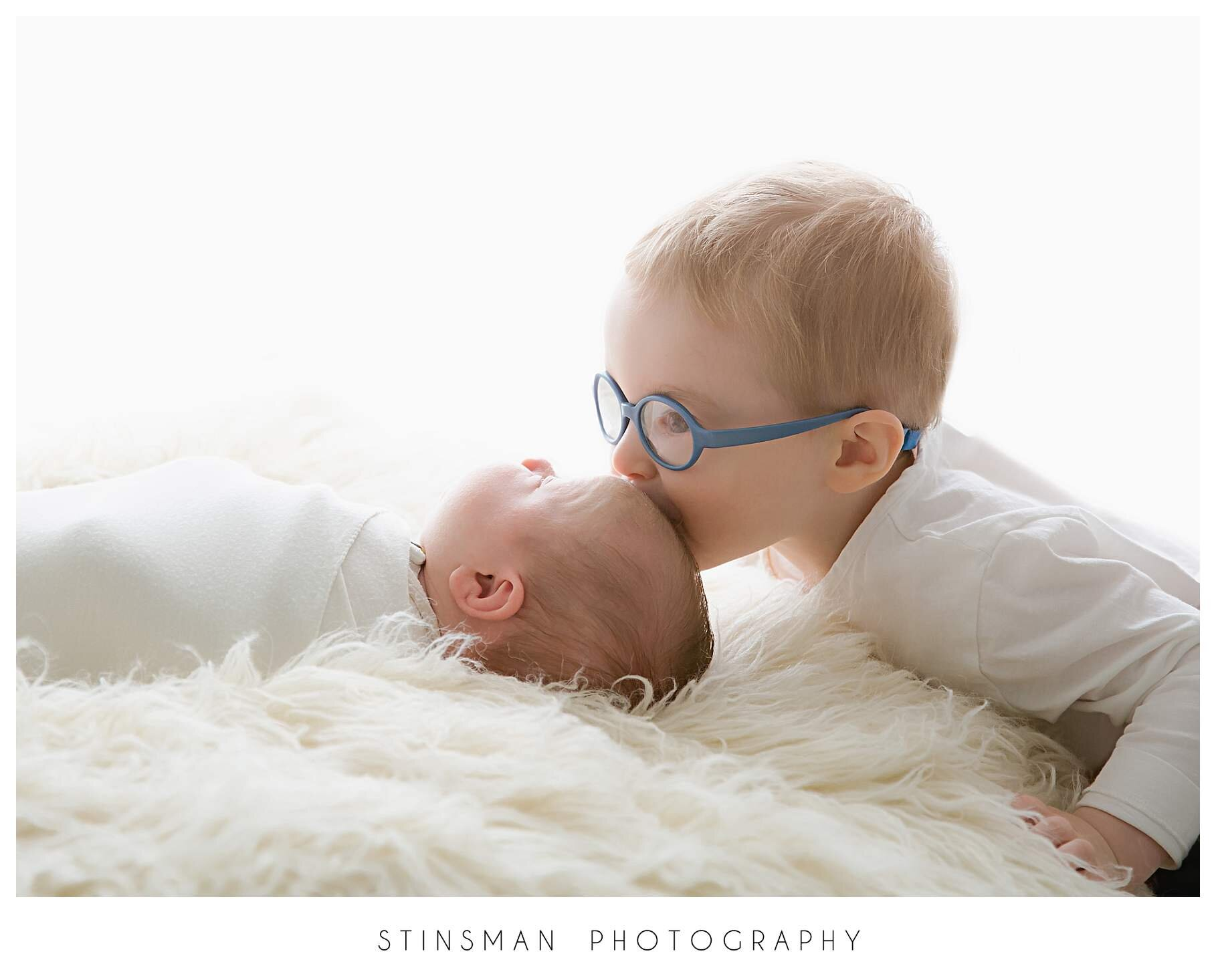 brother kissing baby