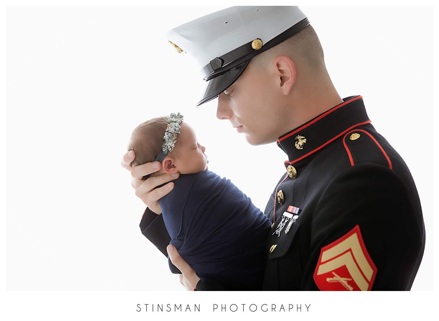 marine dad snuggling his baby girl