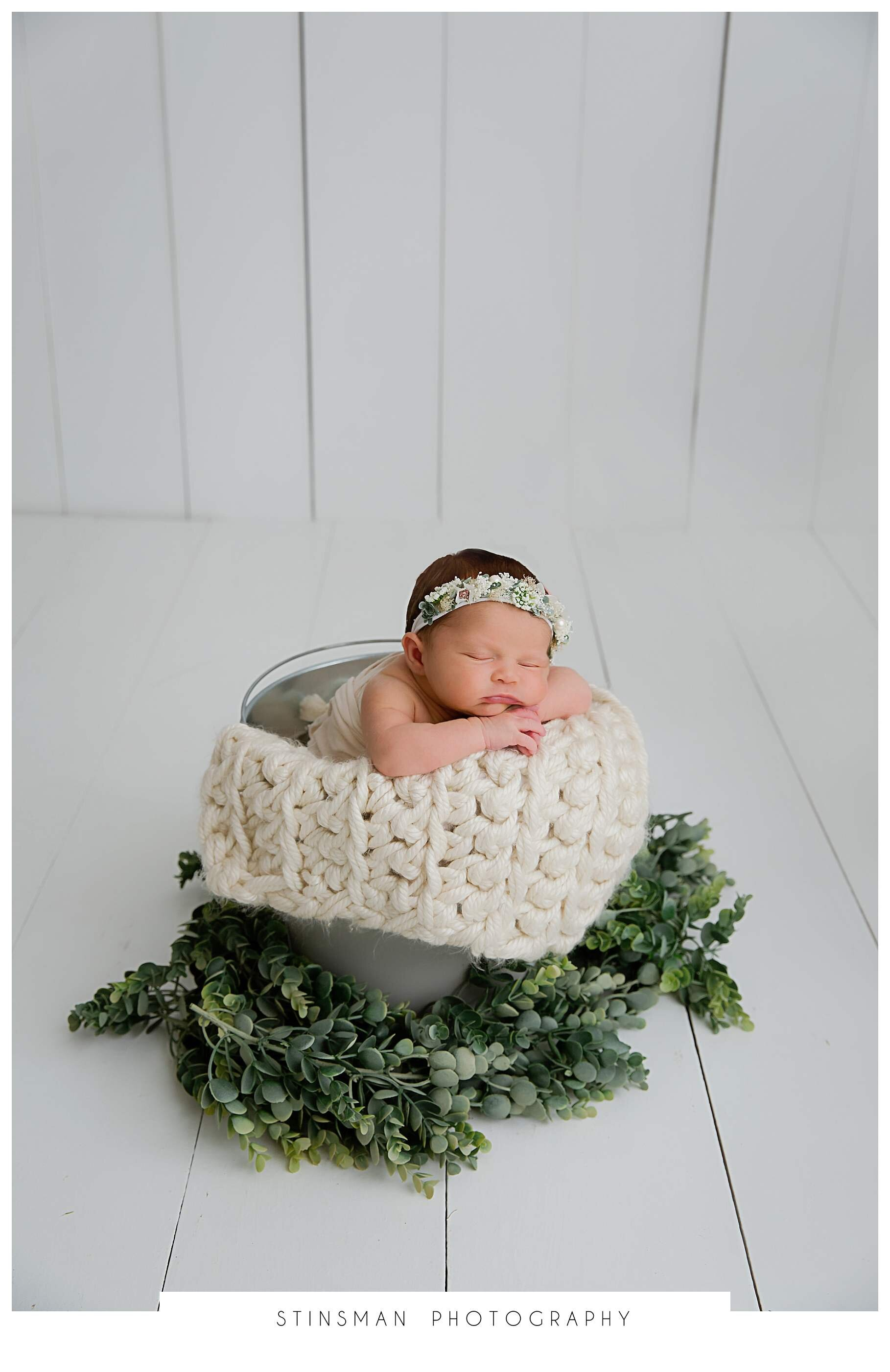 baby girl in a bucket for newborn session