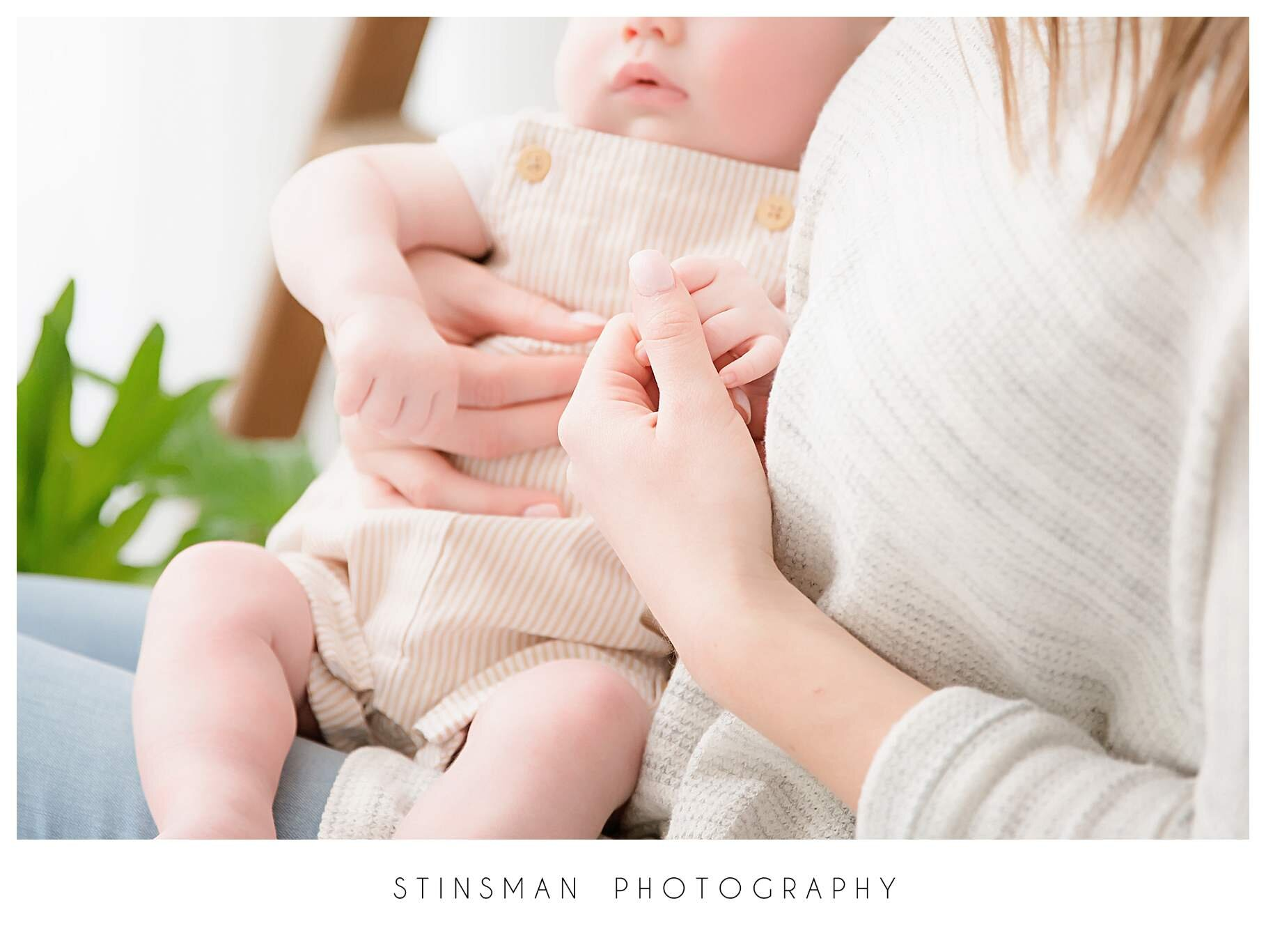 detail photo of mom holding baby hand