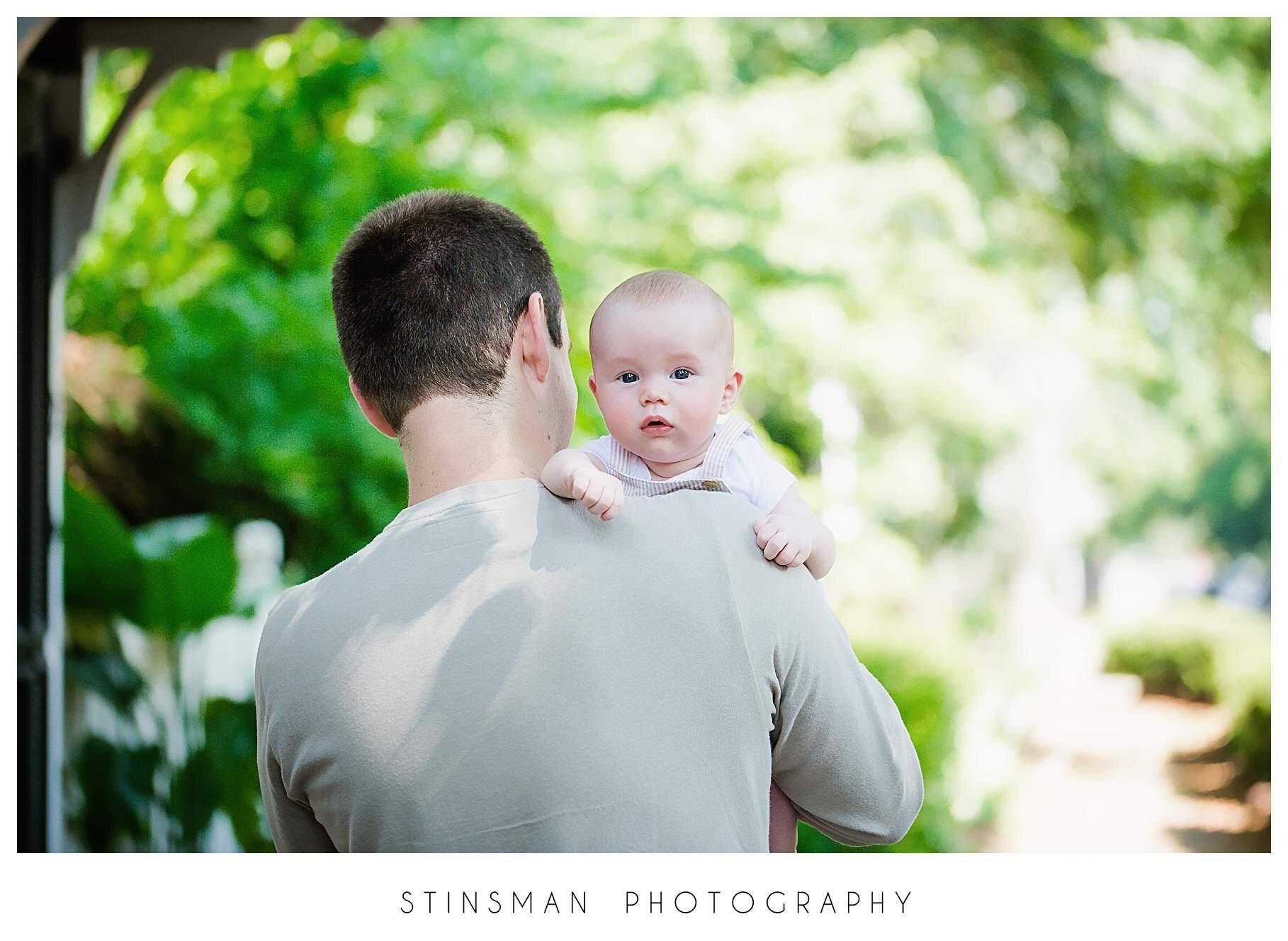 baby boy looking over dad's shoulder