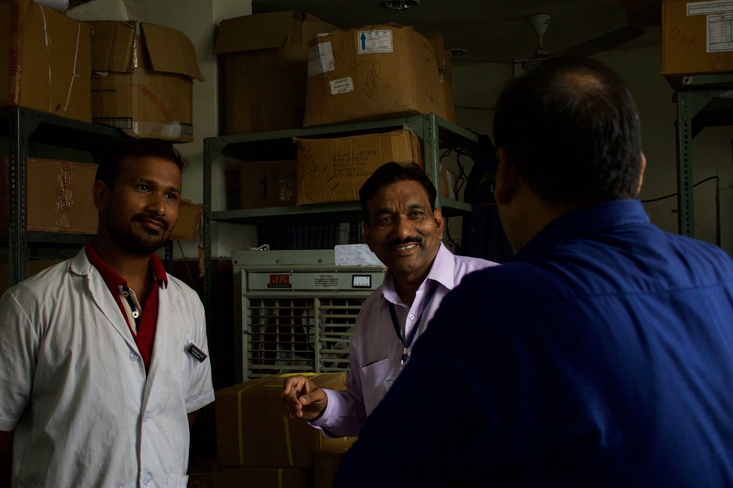 During a visit to Maharana Bhupal Hospital, Dr. Dr. Rajesh Bharadiya stops to check in with Dr. Sanjeev and the pharmacist on duty.