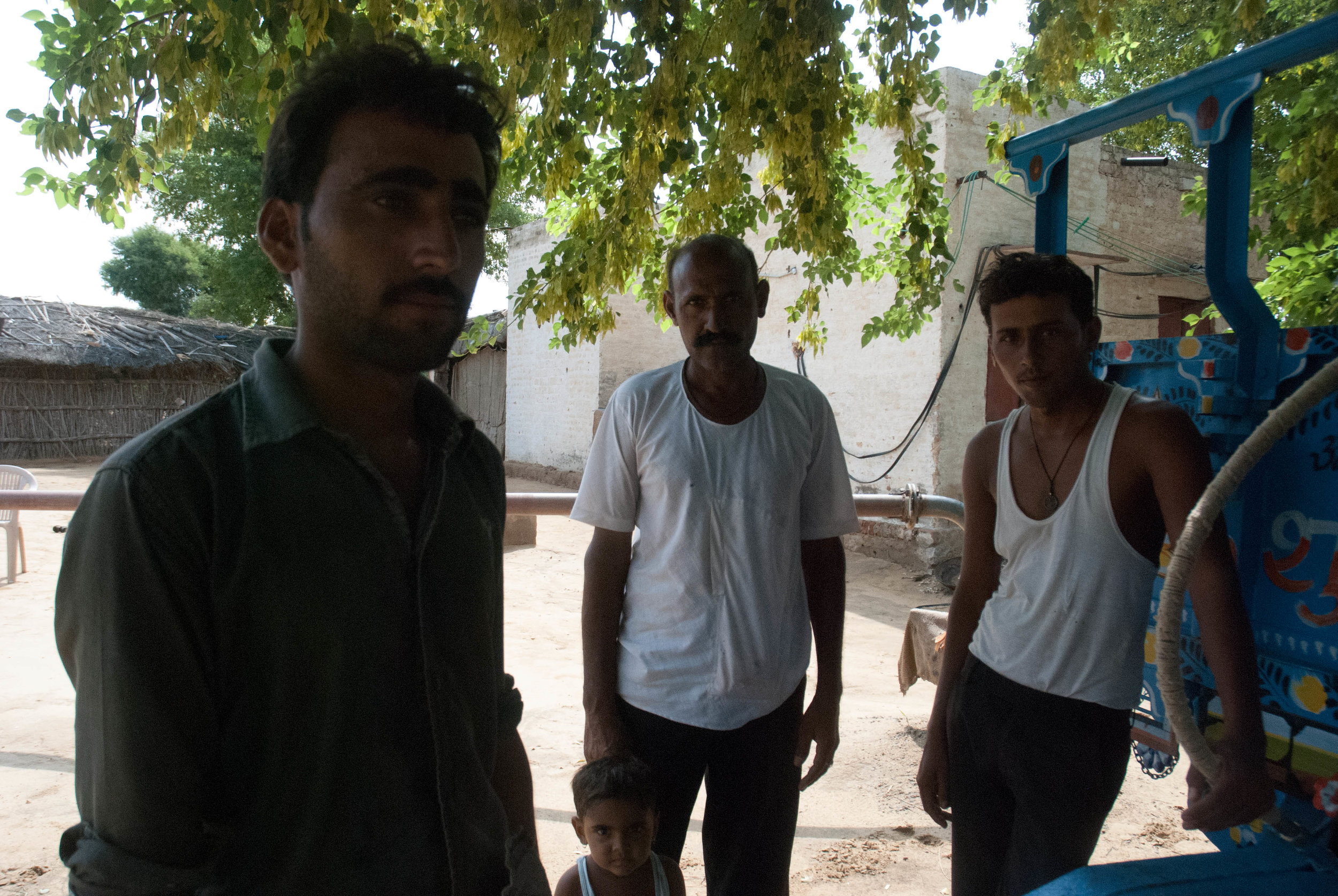 The men of the Siddh family. The father (in the back) works on the farm while his two sons work as tractor drivers.