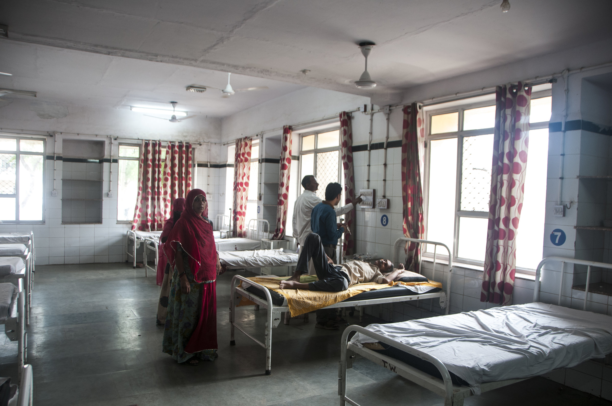 The wife and daughter wait by the newly admitted patient in the General Ward of Chittorgarh District Hospital.