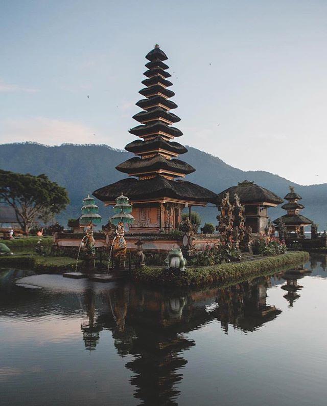 """O templo situa-se numa região montanhosa, à beira do lago Bratan, perto da estância de Bedugul. Fica cerca de 30 km a sudeste de Singaraja e 50 km a norte da capital da ilha, Dempassar.  Foi construído em 1633 e nele é venerada a deusa da água, dos rios e dos lagos Dewi Danu. É por isso um dos chamados """"templos da água"""", associados ao sistema de irrigação tradicional balinês subak. Devido à importância do lago Bratan como principal fonte da irrigação do centro do Bali, nele são realizadas cerimónias onde são feitas oferendas. A principal pelinggih meru (""""torre Meru""""), caraterística dos pura (templos hindus balineses) tem 11 andares (telhados) e é dedicada ao deus Xiva e à sua consorte Parvati. No interior do complexo há também uma estátua de Buda. .pic by @evandrorocha . . . . #bali #indonesia #temple #ulundanuberatanbali #hindu #nature #photography #photographer #photooftheday #picoftheday #travel #trip #mytrip #viagem #ferias #melhoresdestinos #lugaresincriveis"""