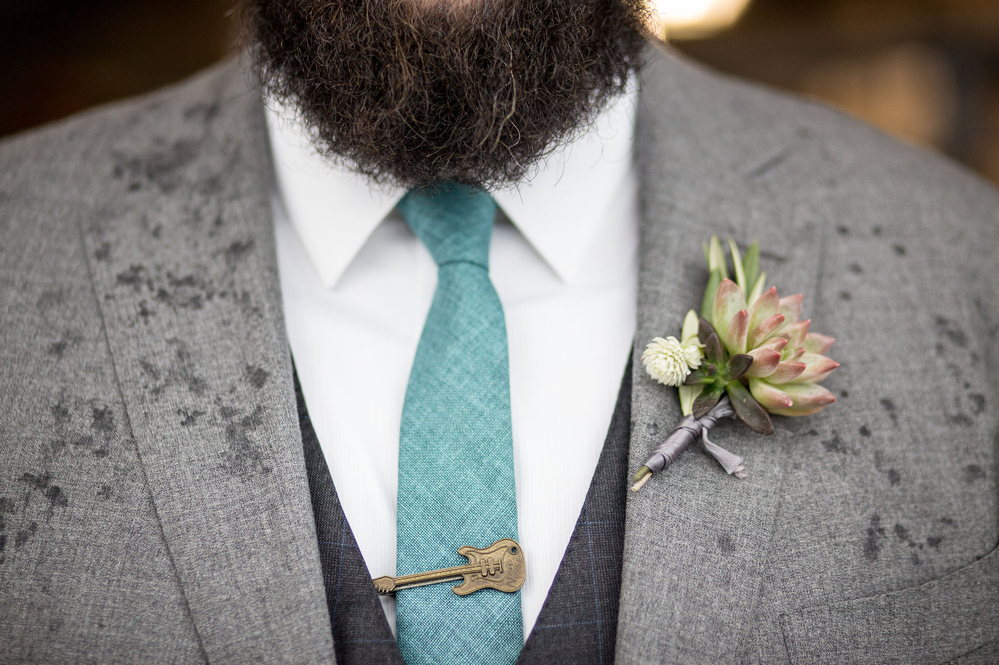 Accessories for the groom - like this awesome guitar tie clip and succulent boutonniere