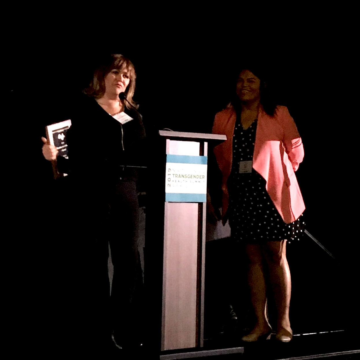 Karen Aguilar accepting her award after introduction by Jenna, member of the SF AFFIRM Community Advisory board.