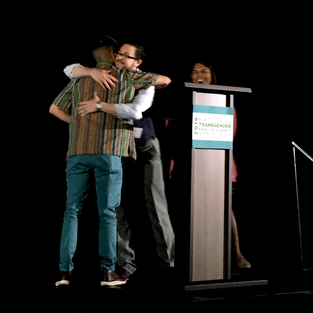 Seth and Tố hug at the speakers' podium