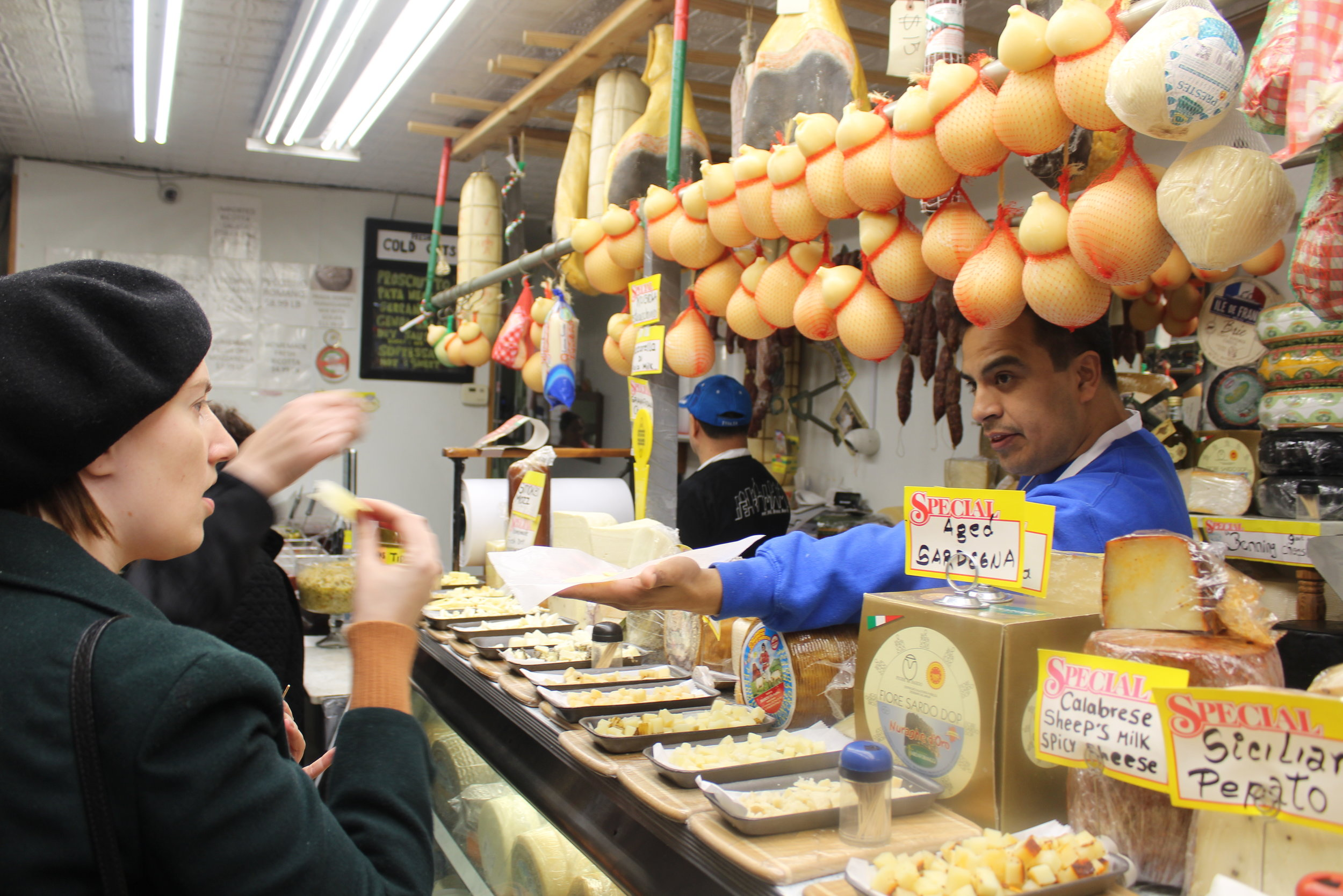 Abram, a former chef offers samples of caciocavallo cheese (shown in the red netting) to our tour guests at Calandra's.