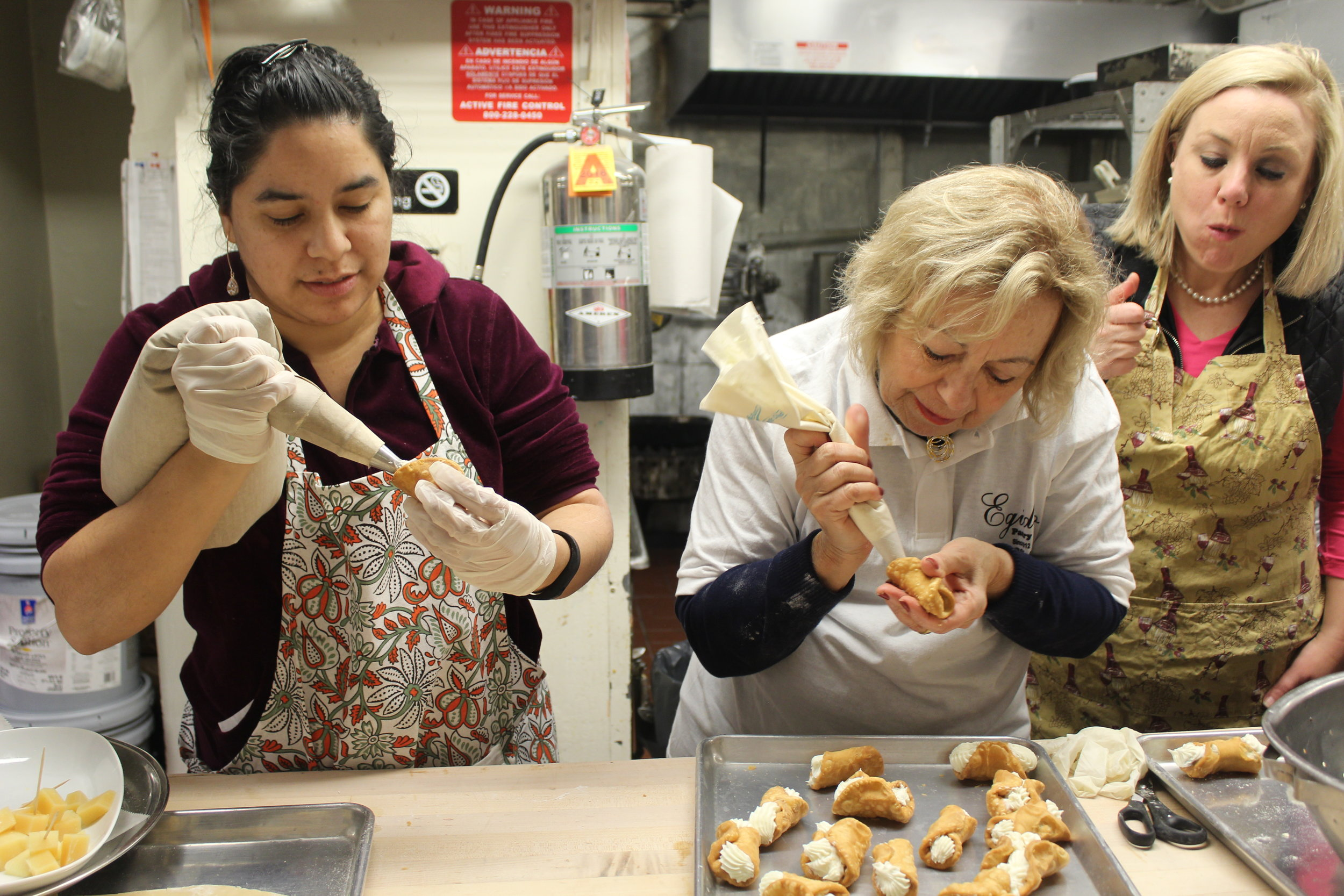 Guests at our cannoli class at Egidio Pastry Shop learn how to fill cannoli.
