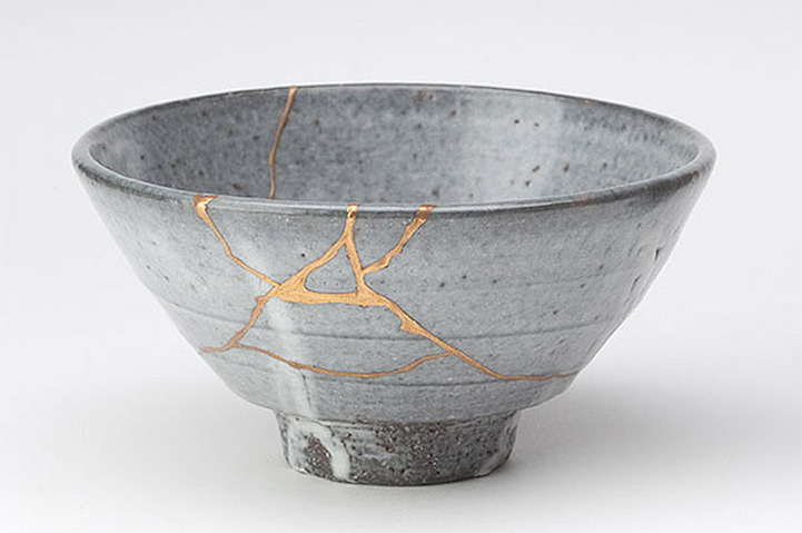 "Kintsugi  (or  Kintsukuroi , which means ""golden repair"") celebrates the is the centuries-old Japanese art of fixing broken pottery with a special lacquer dusted with powdered gold, silver, or platinum. Beautiful seams of gold glint in the cracks of ceramic ware, giving a unique appearance to the piece.  This repair method celebrates each artifact's unique history by emphasizing its fractures and breaks instead of hiding or disguising them. Kintsugi often makes the repaired piece even more beautiful than the original, revitalizing it with new life."