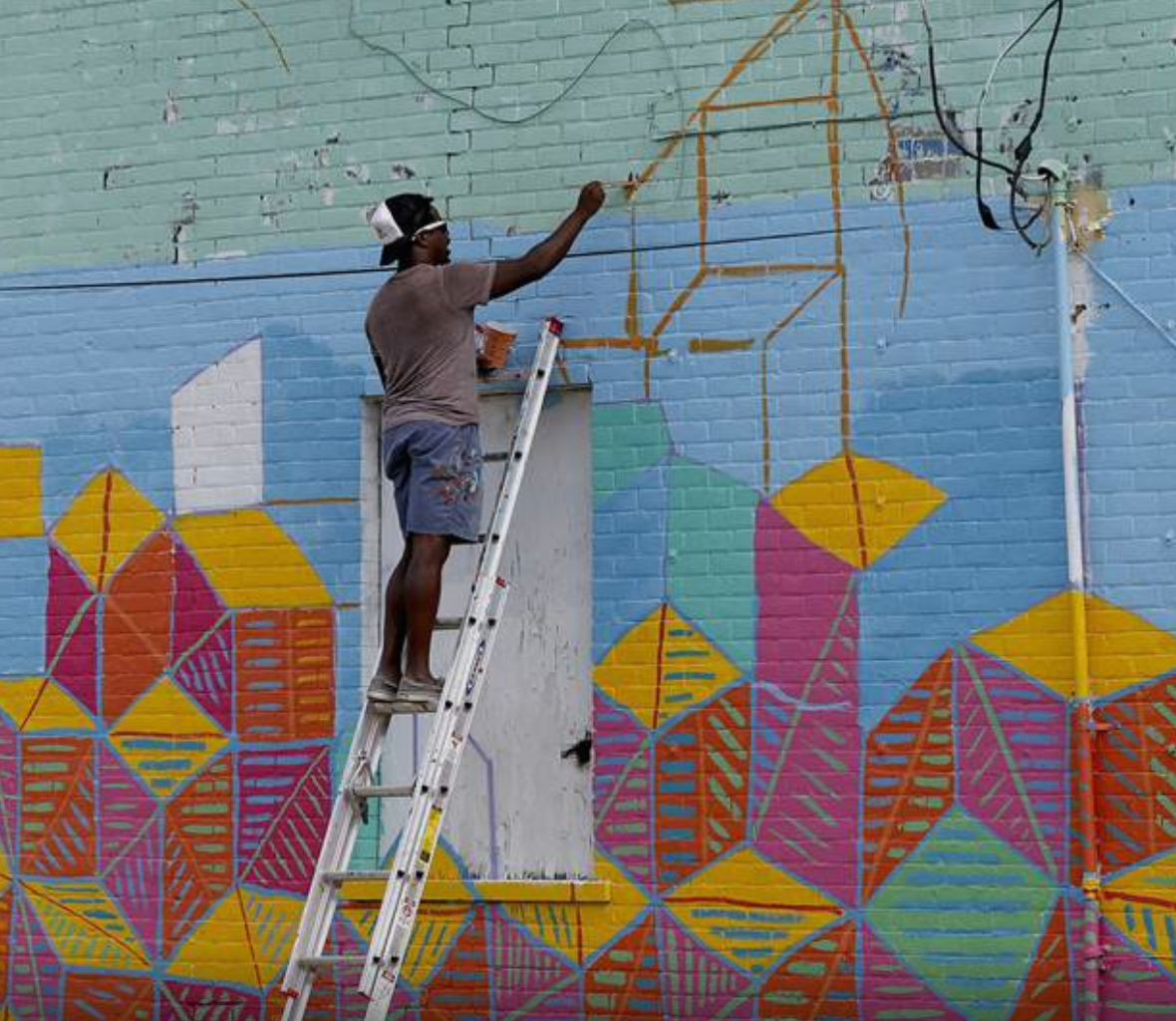Artist Yusuf Lateef works on a mural on Detroit Avenue in Toledo.  Source: The Blade/Lori King