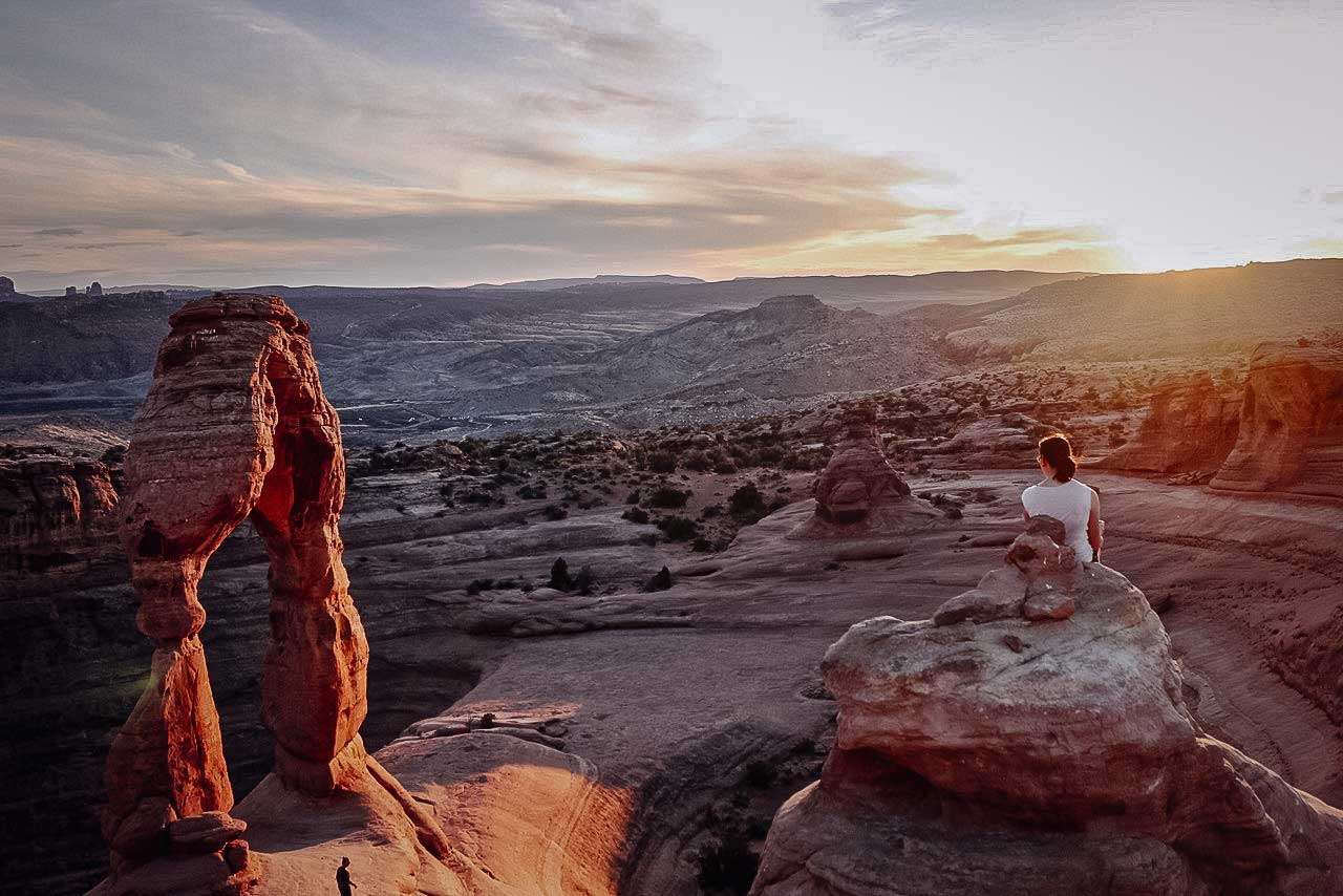 A woman enjoys the silence during sunset at Arches National Park.  Shot by Ryan.