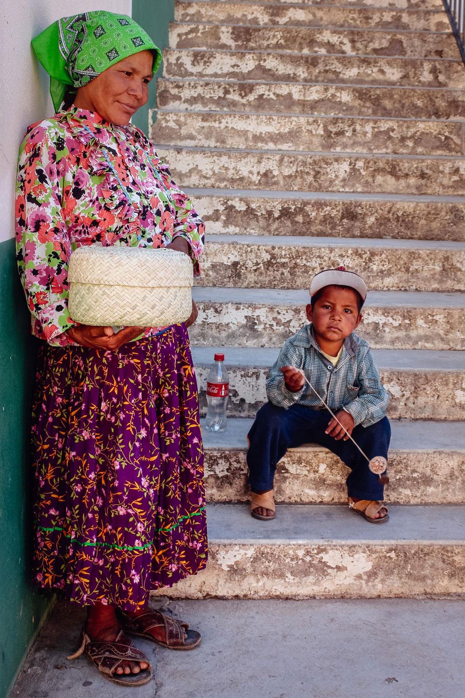 A Raramuri woman presents a hand-woven basket while her son plays with a yo-yo.
